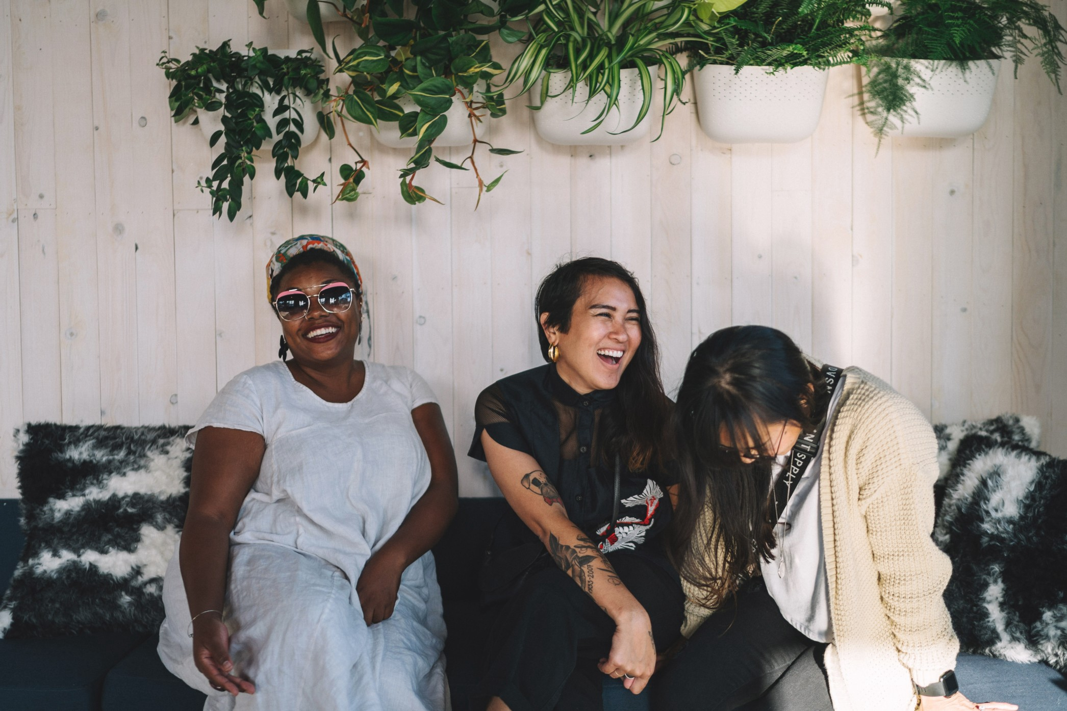 Three women laugh together in the afternoon light.
