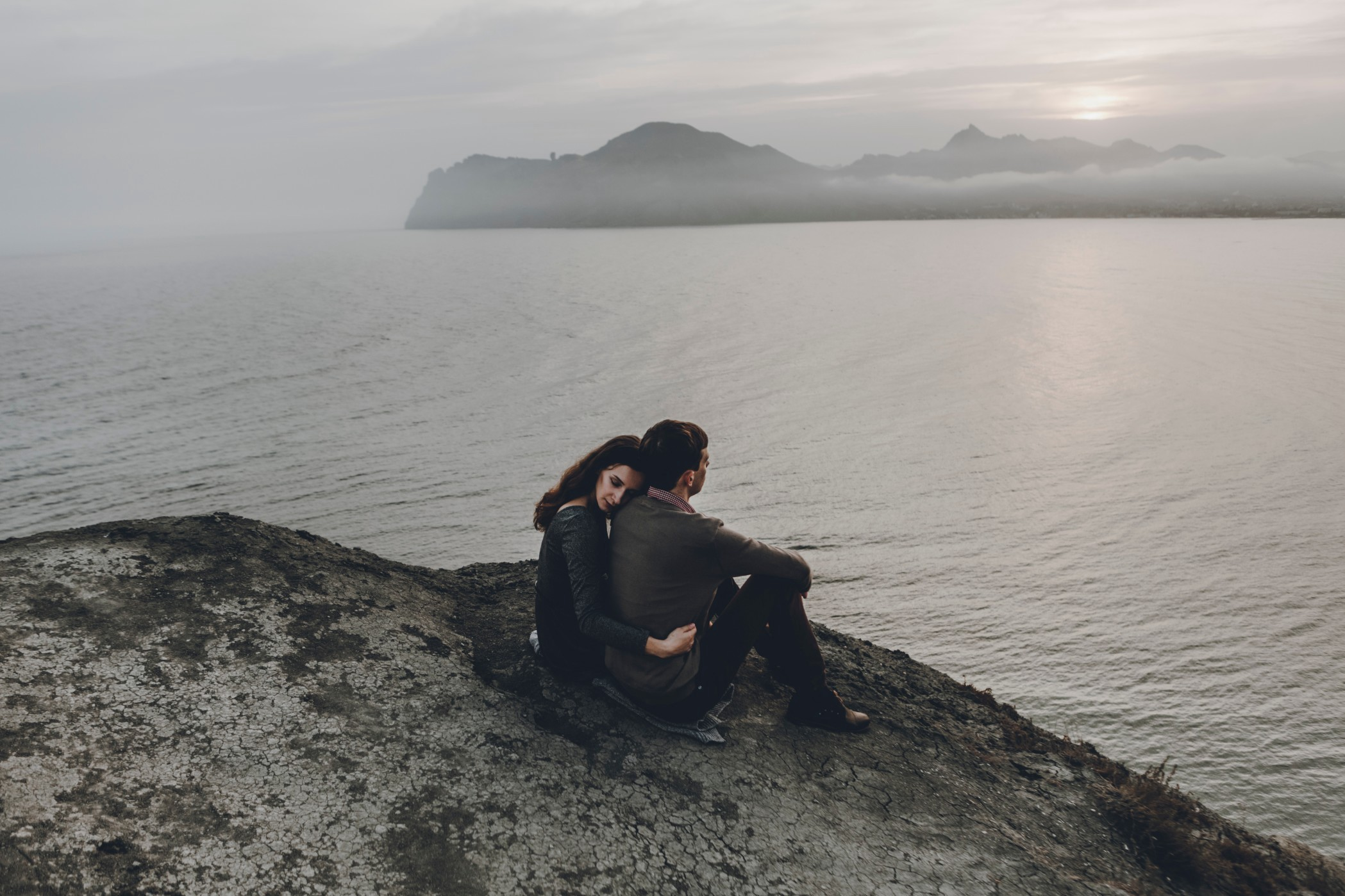 A couple embraces on a cliff overlooking a grey and cloudy sea.
