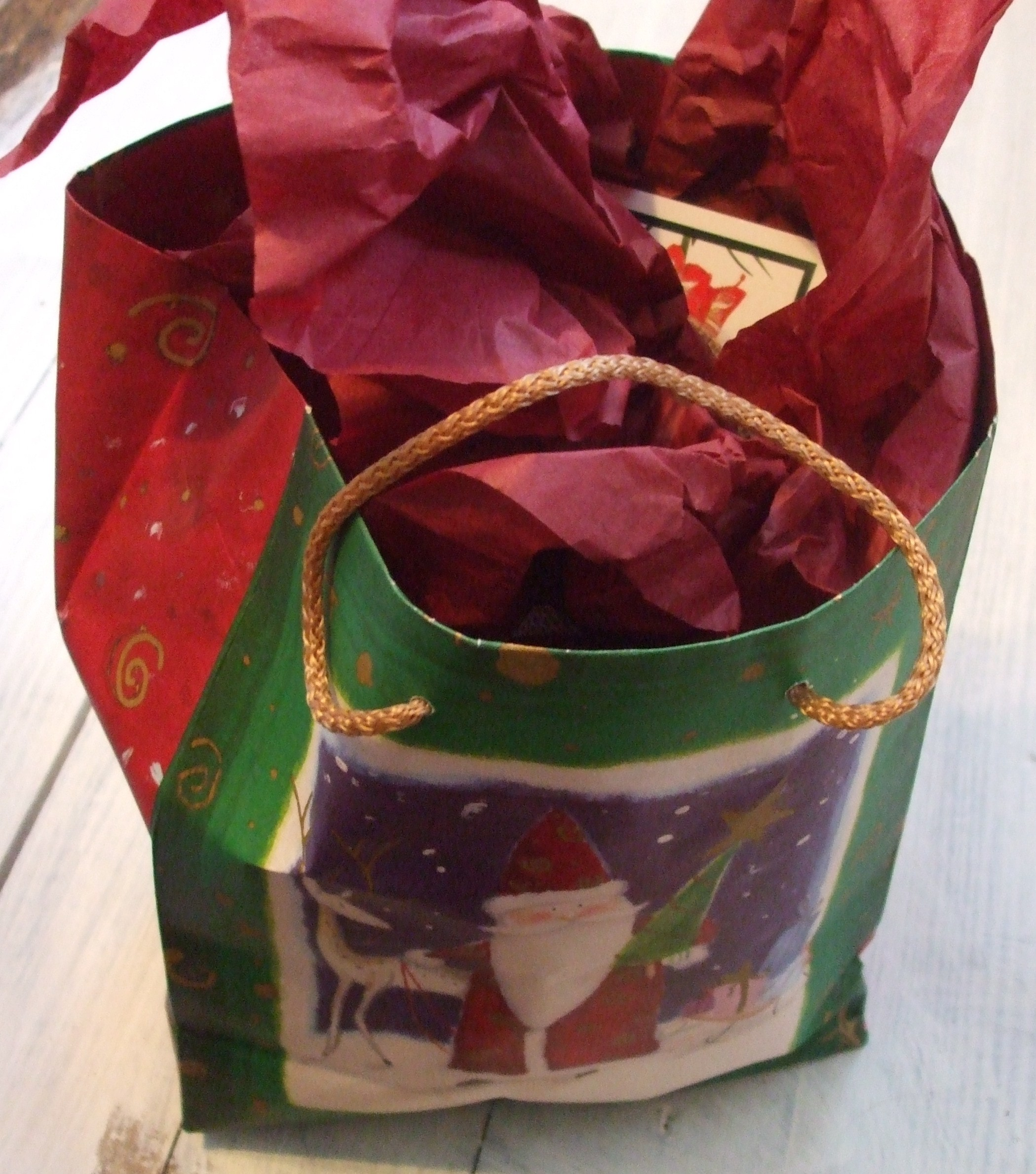 A gift bag with red and green decorations and red tissue paper.