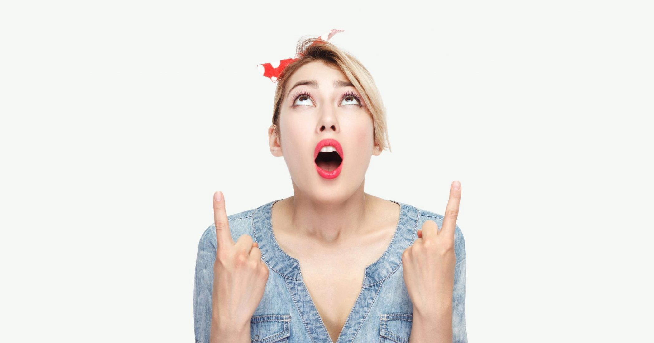 Woman with mouth open in surprise, her hands raised with fingers pointing up