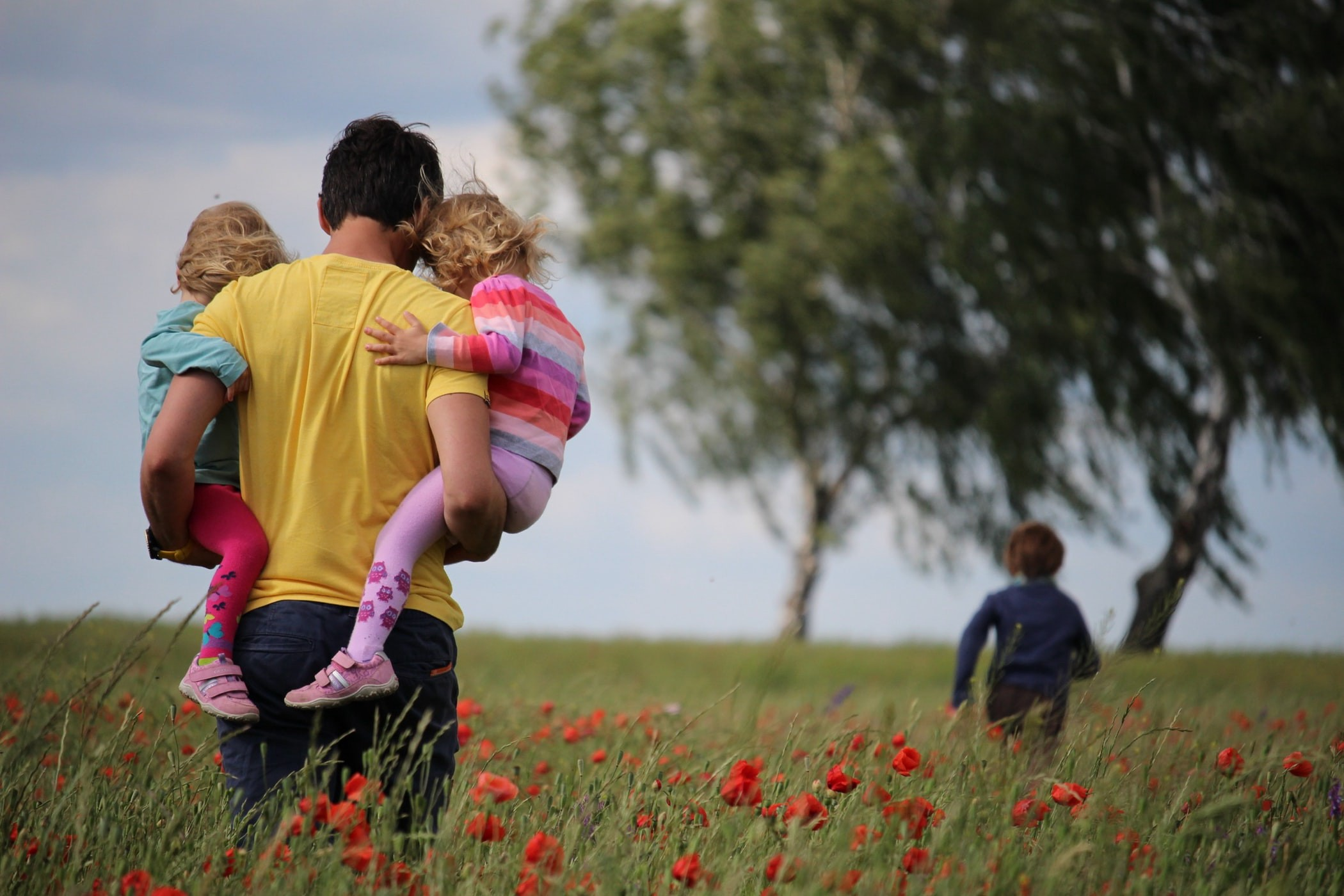 A father carrying two daughters while his son runs through a field of flowers.