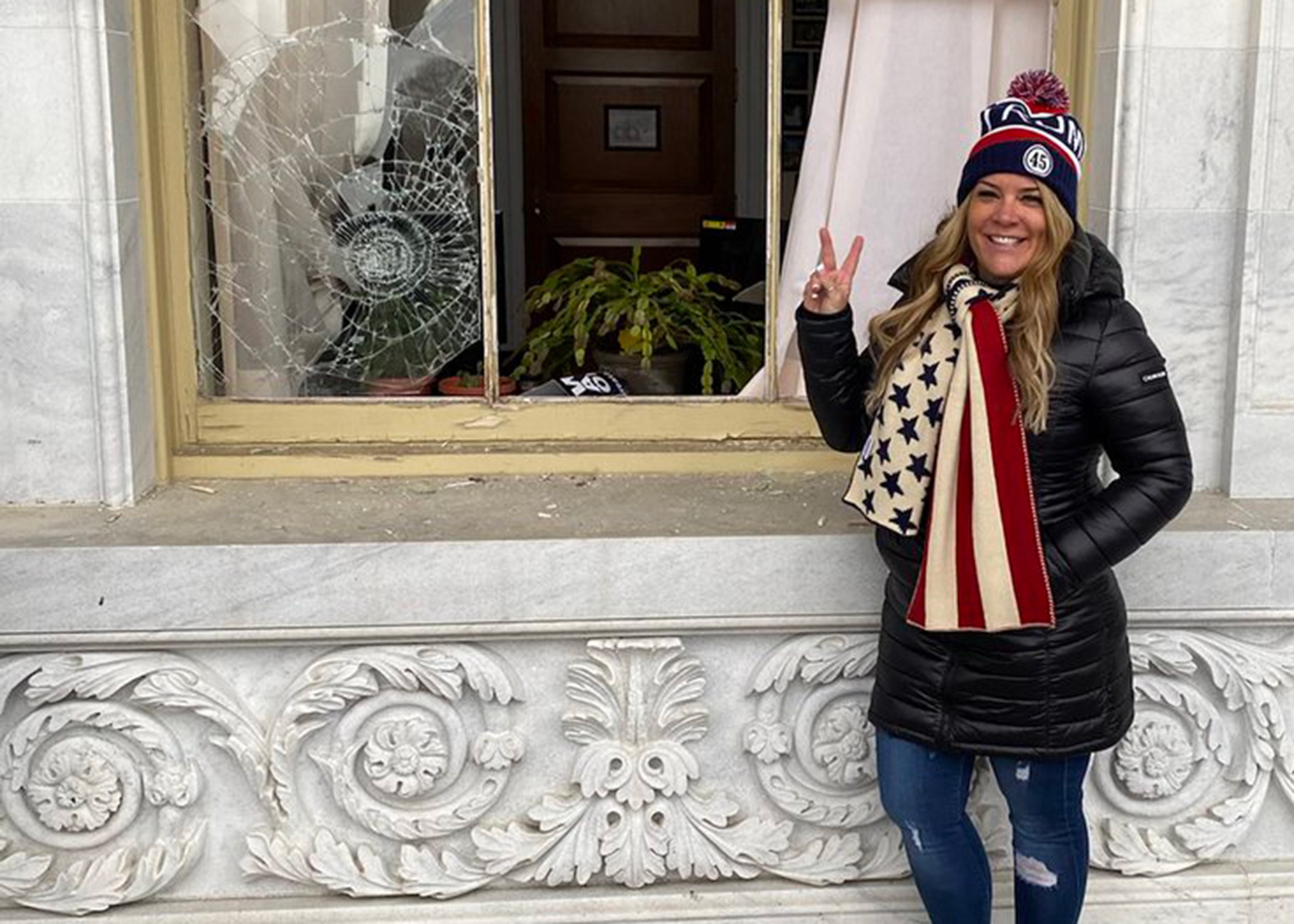 Image from the Twitter account of @DotJenna showing her flashing a peace sign outside a broken Capitol building window.