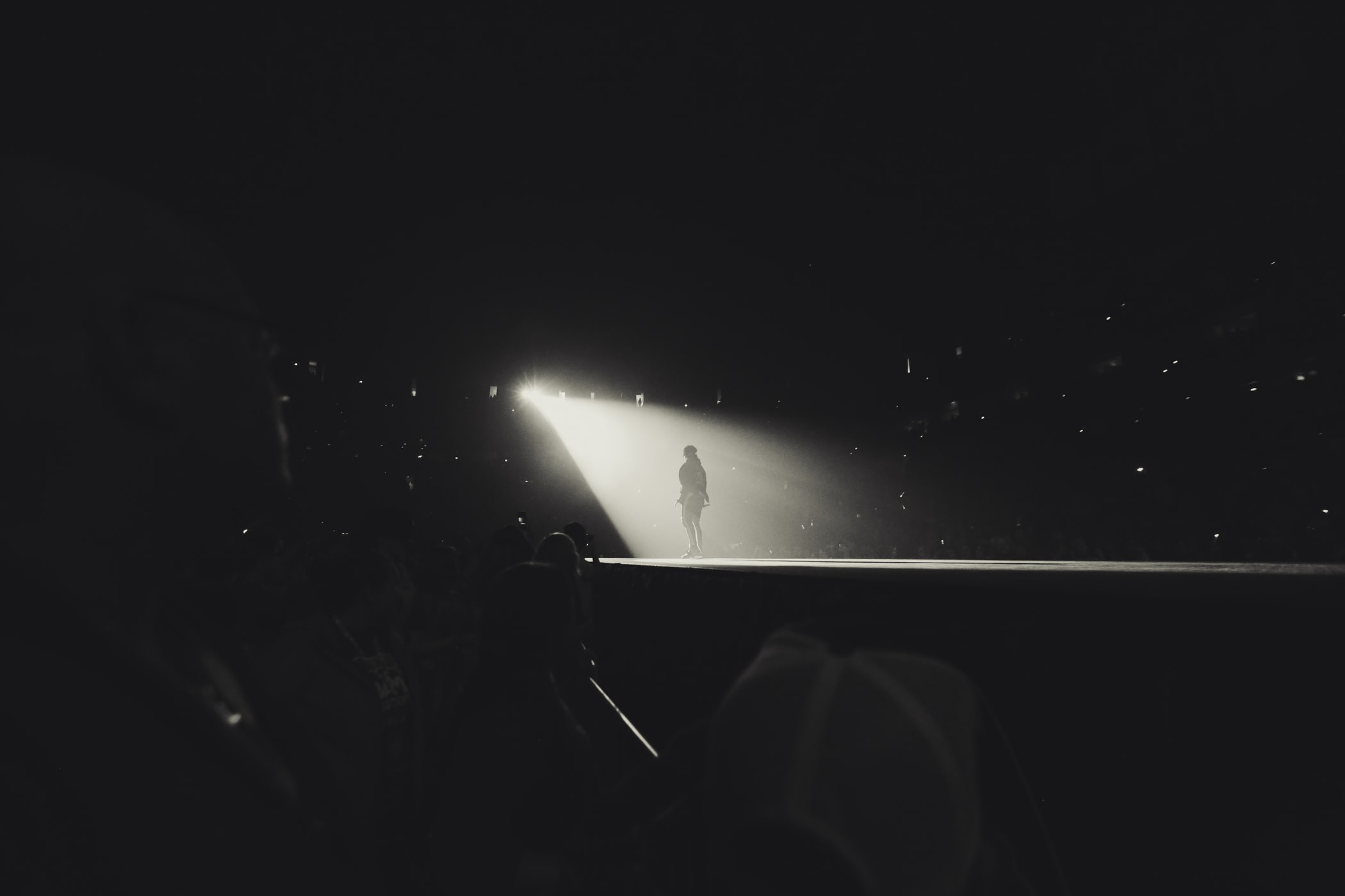 Black and White Photograph with a single person on stage back to camera, spotlight shining brightly.