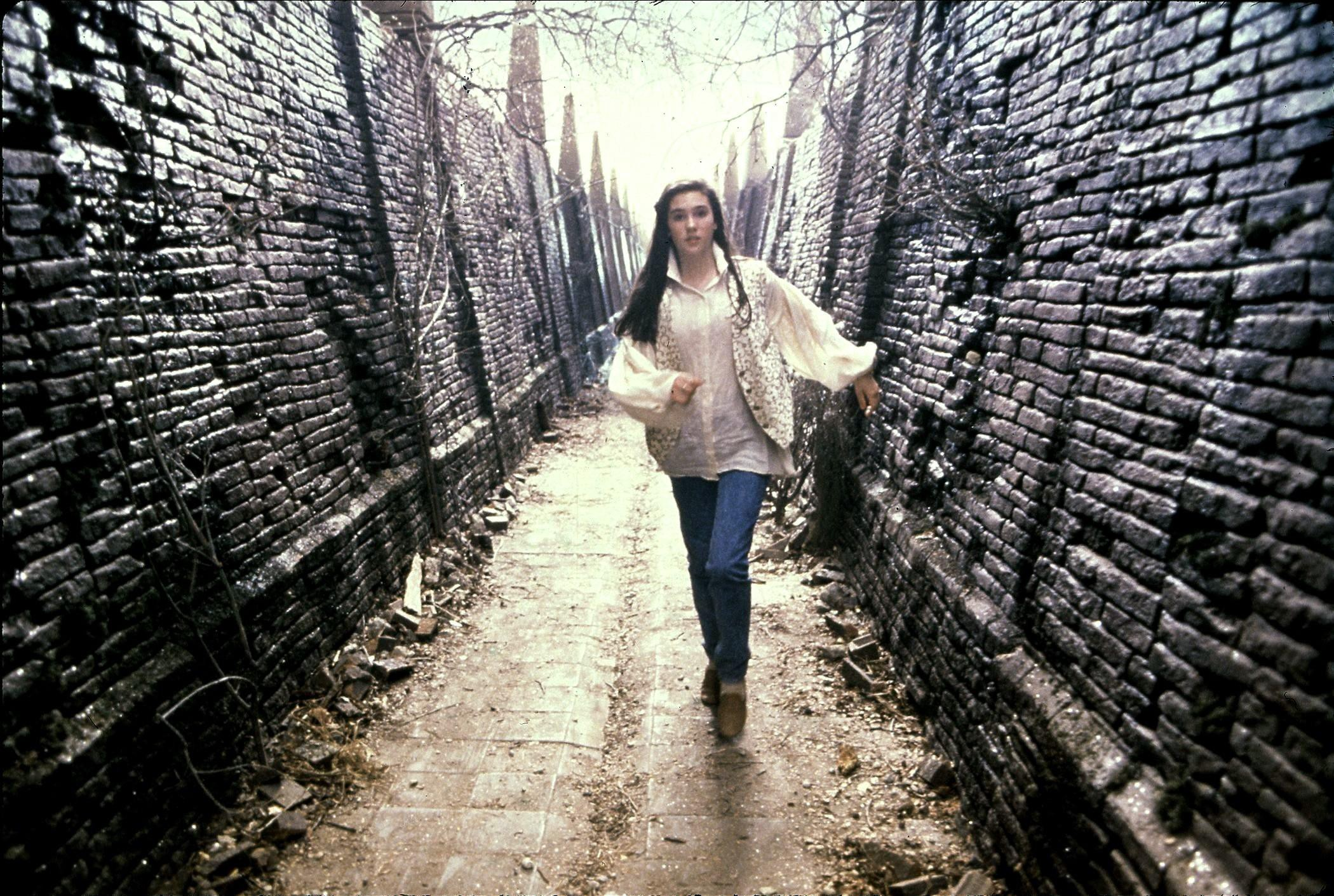 A scene from the movie Labyrinth: A young, white woman in a white poet's blouse, vest, and jeans runs along a desolate labyrinth hallway with broken bricks and dead vines on an overcast day.