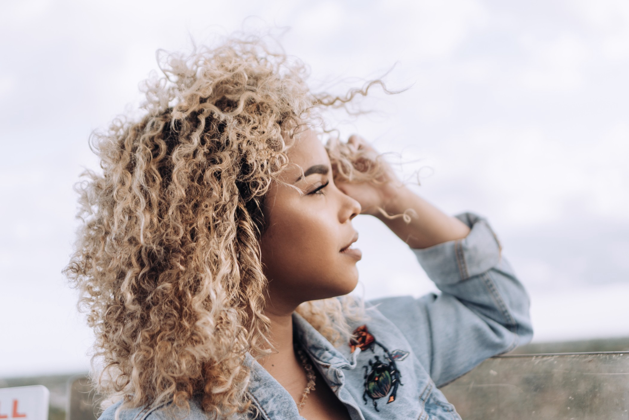 A woman with curly blonde hair stares into the distance hopefully.