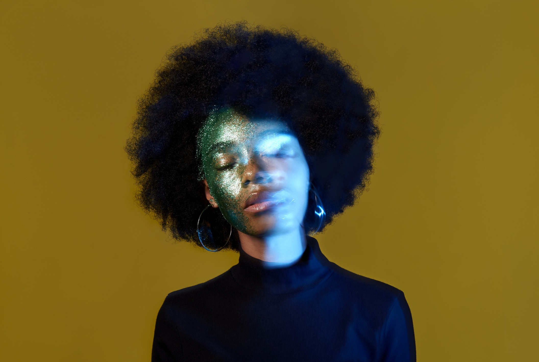 A conceptual portrait of a black woman with glitter on her face, with her face slightly blurred/double exposed.