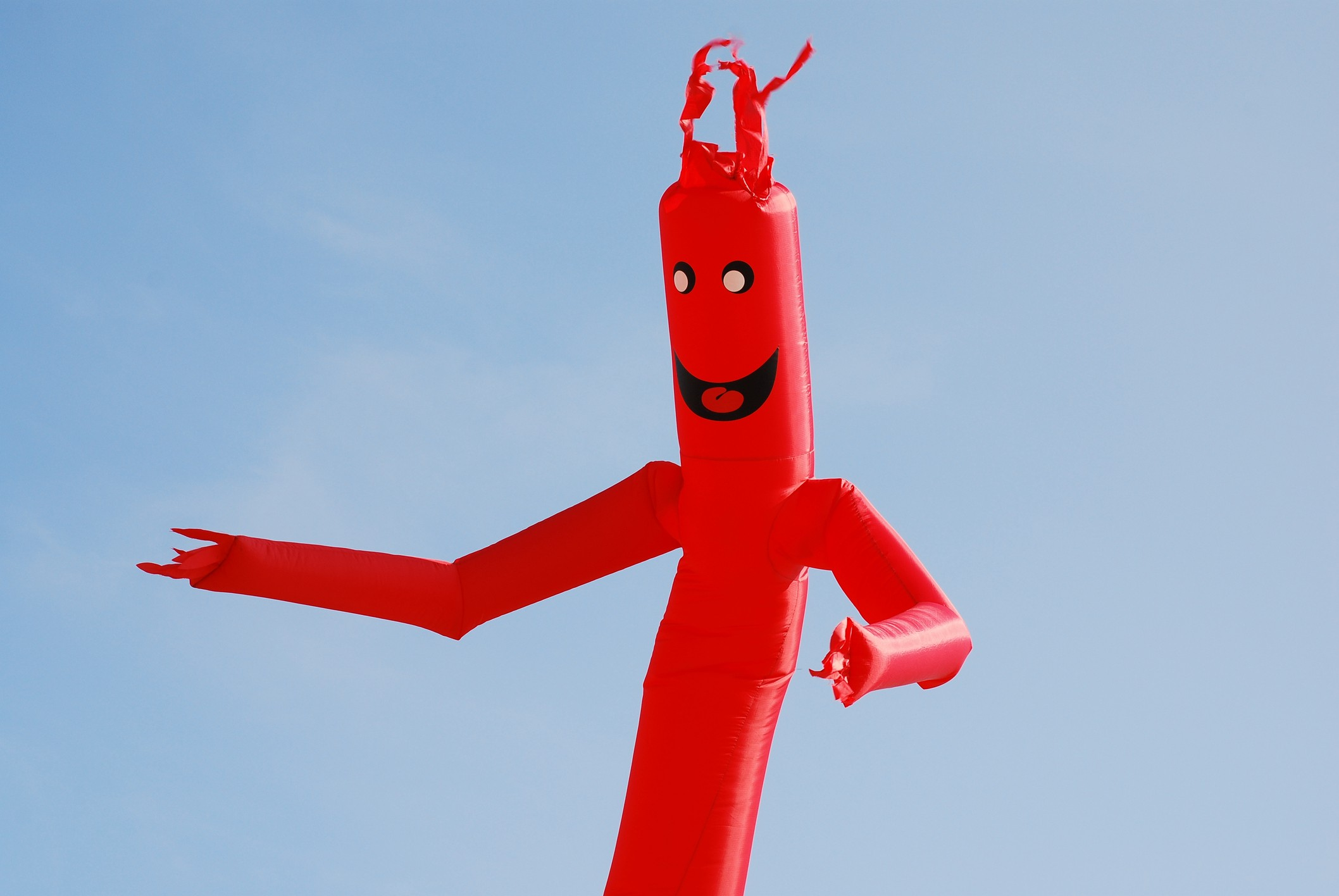 A photo of a red inflatable tube man against a clear blue sky.