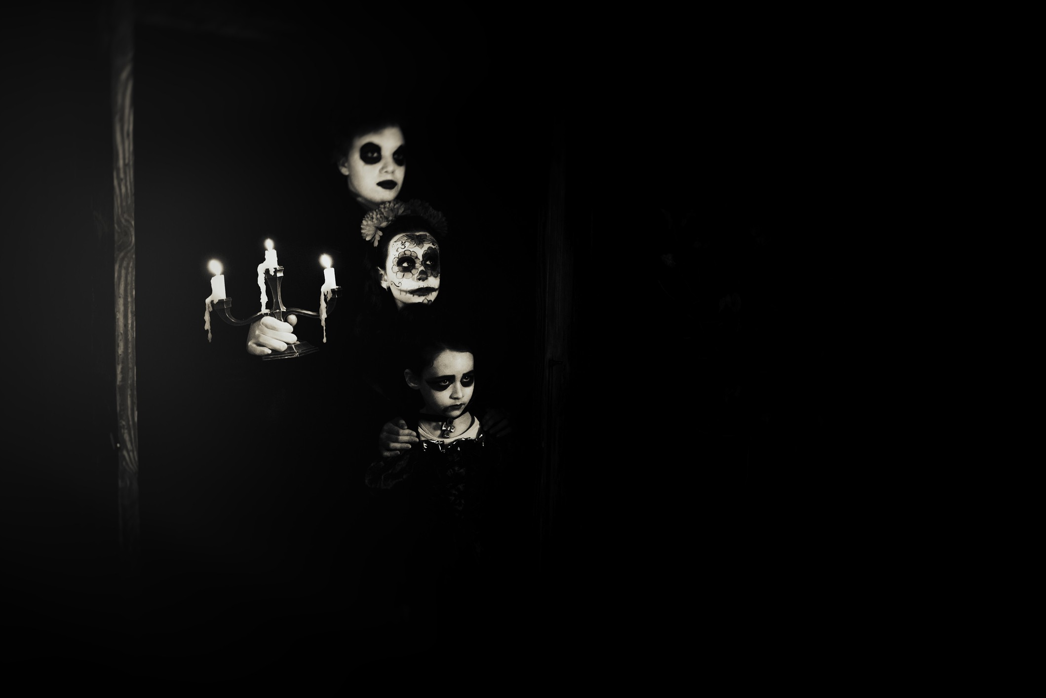 Black and white spooky image of floating Halloween faces.