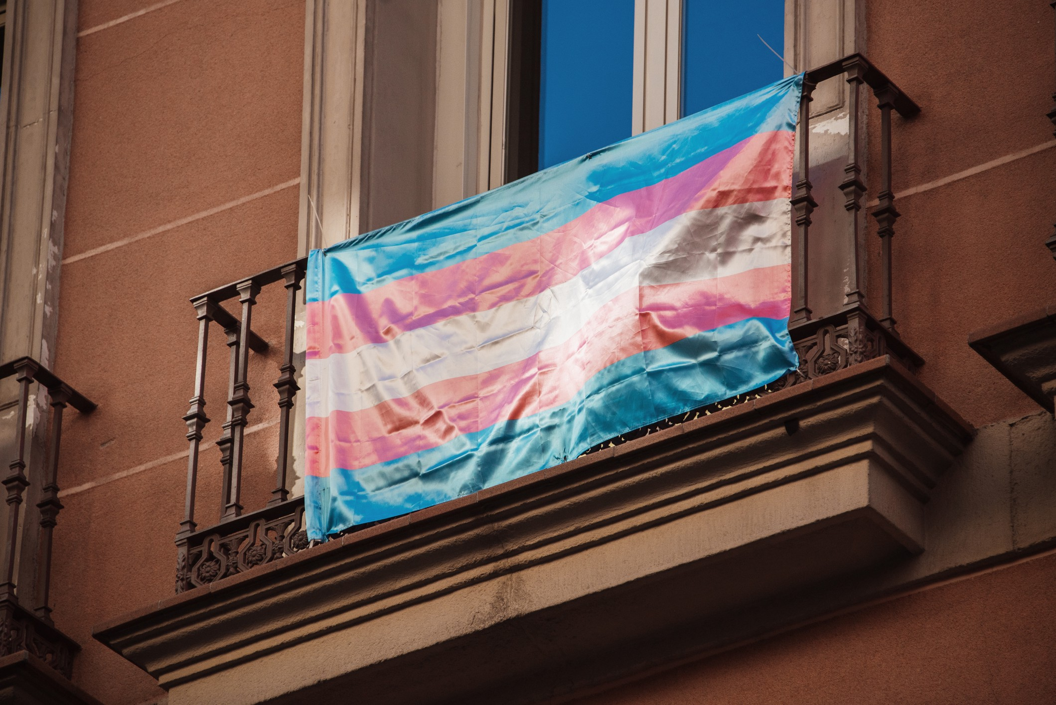 A photo of the trans flag hanging on a balcony.