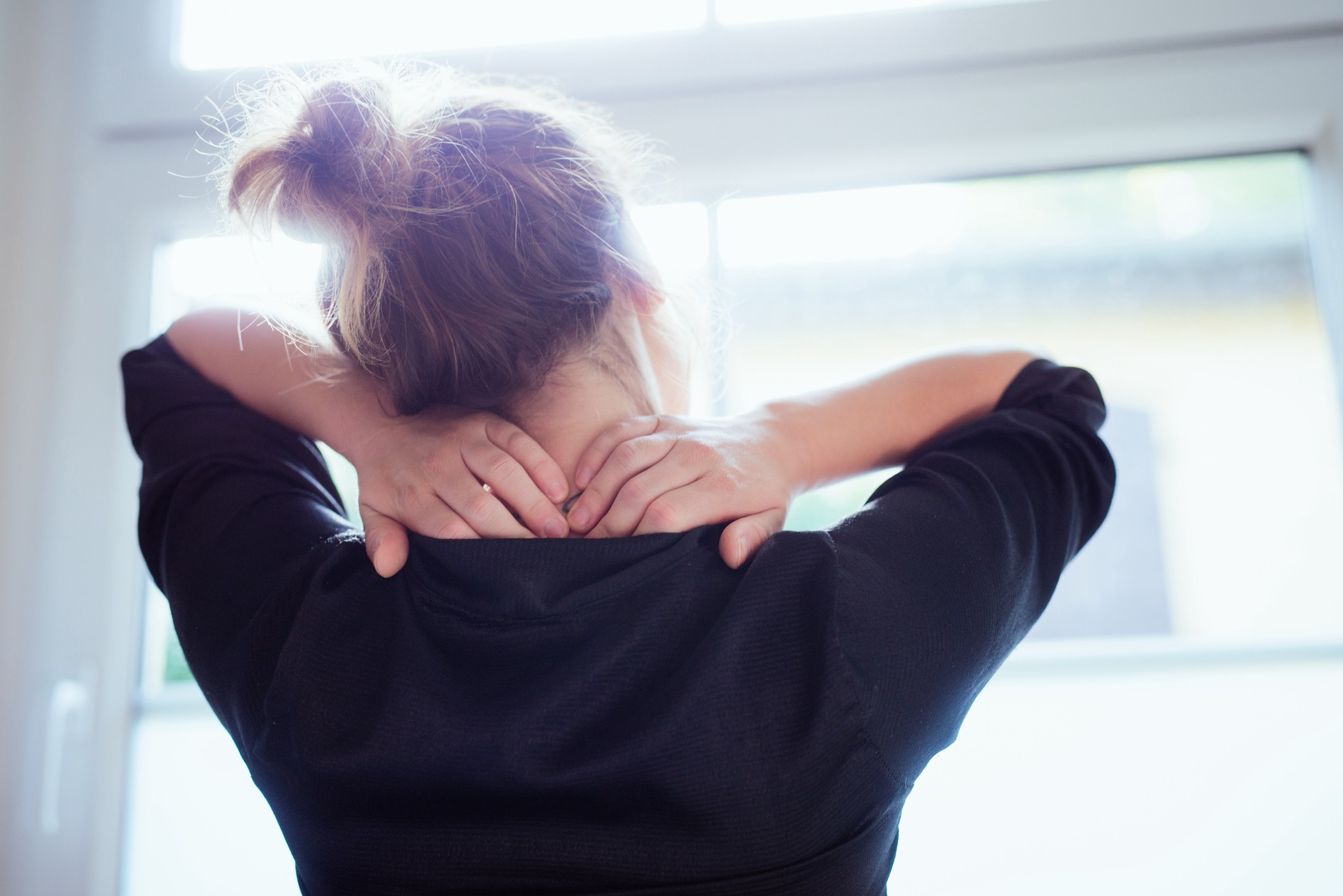 Rear view of a young woman looking out the window as she massages her neck.