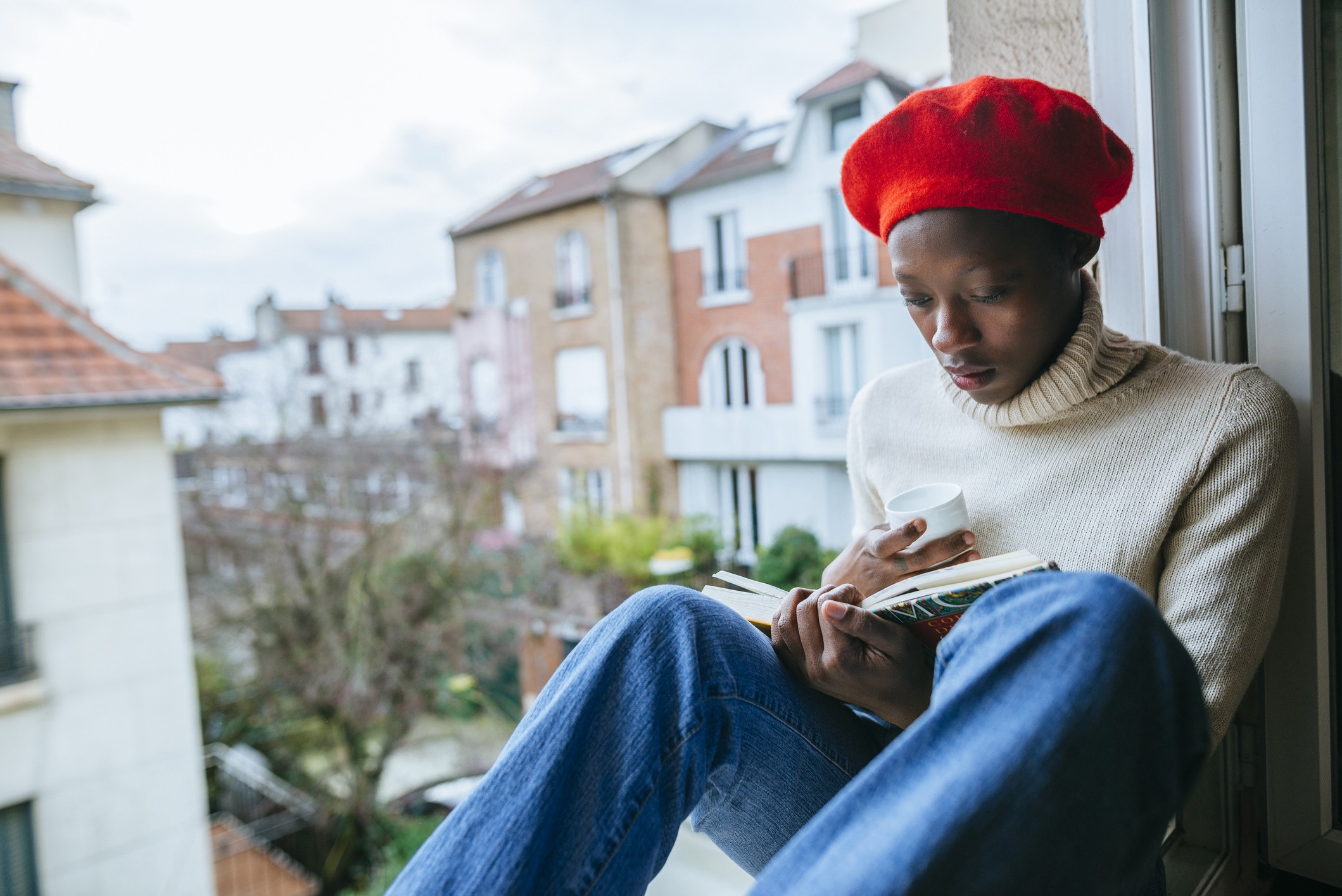 A photo of a young black woman reading by her window.