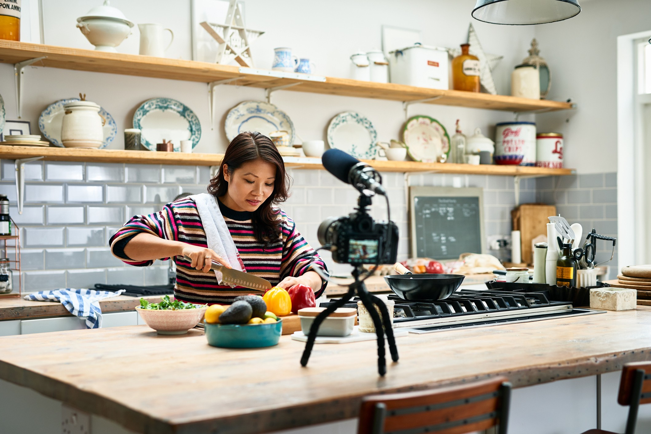 Adult woman preparing a meal and chopping fresh ingredients in front of a video camera on a tripod.