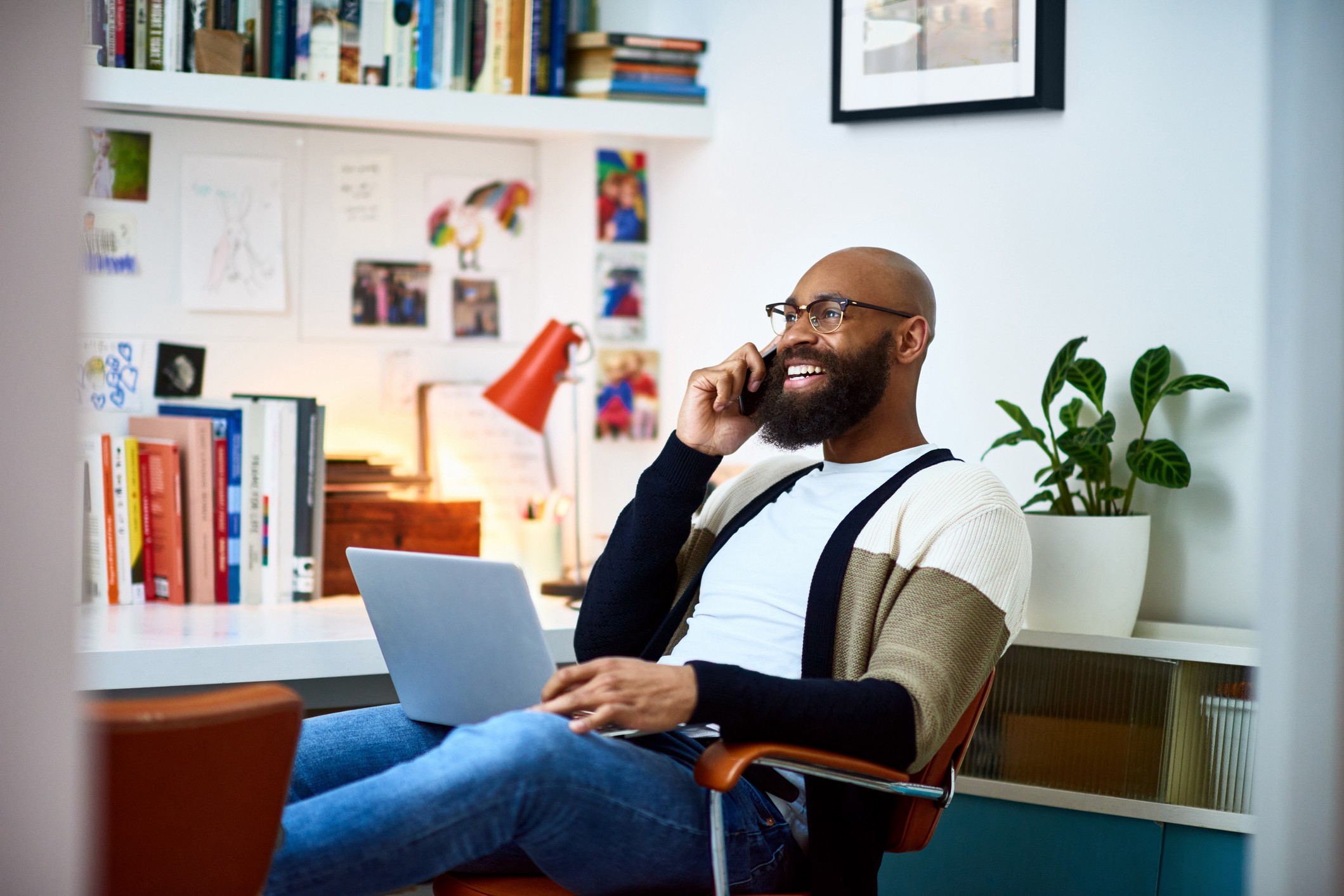 Man smiling as he talks on the phone with someone.