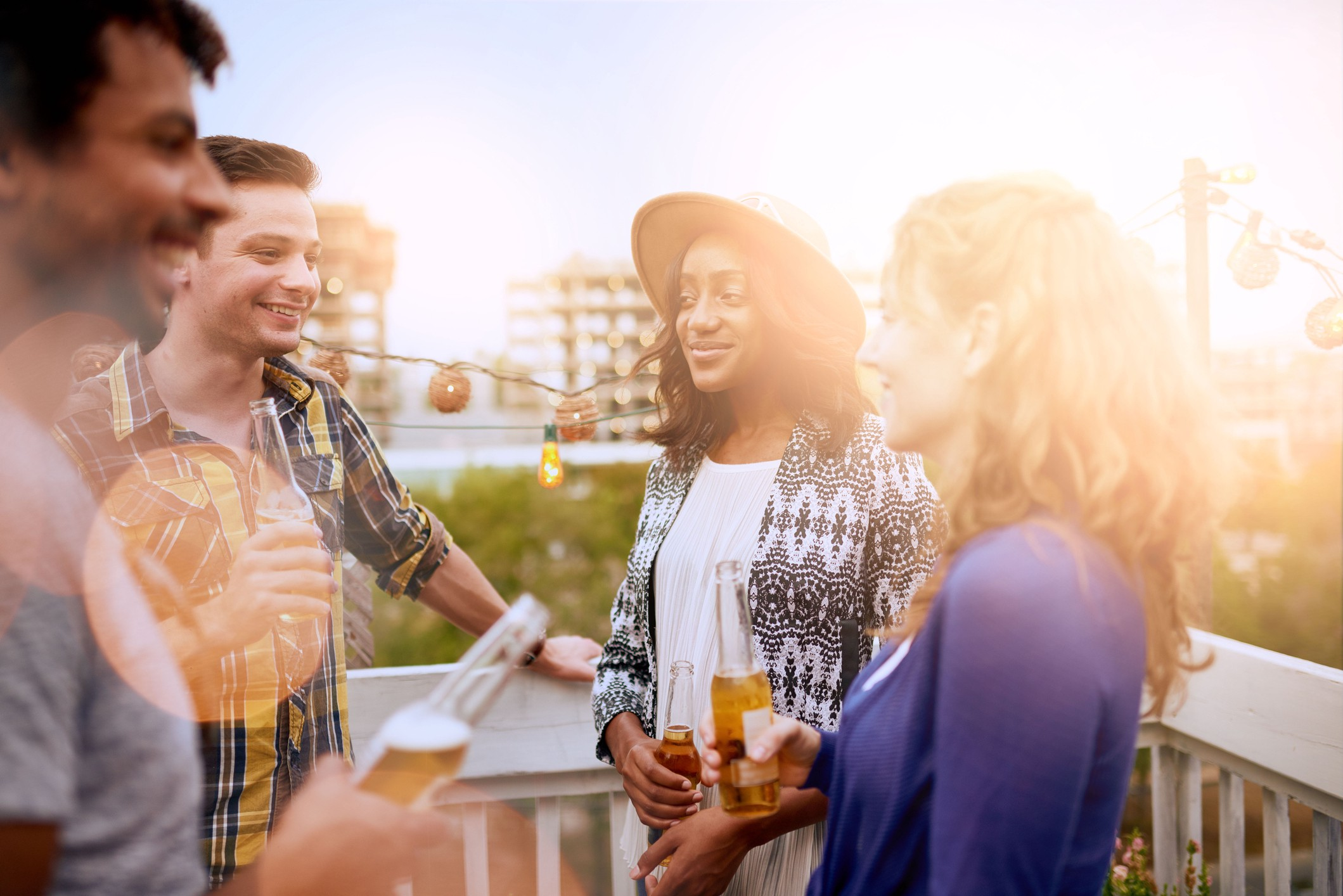 Four people standing with drinks on a deck.