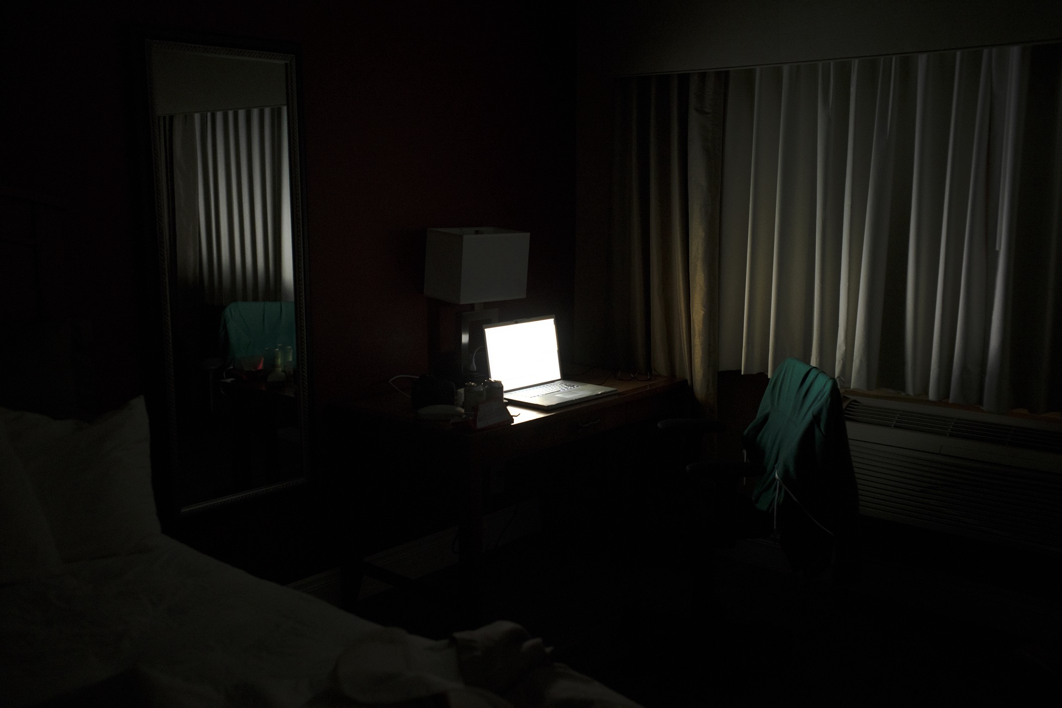 Only a bright laptop screen is visible in this dark room.