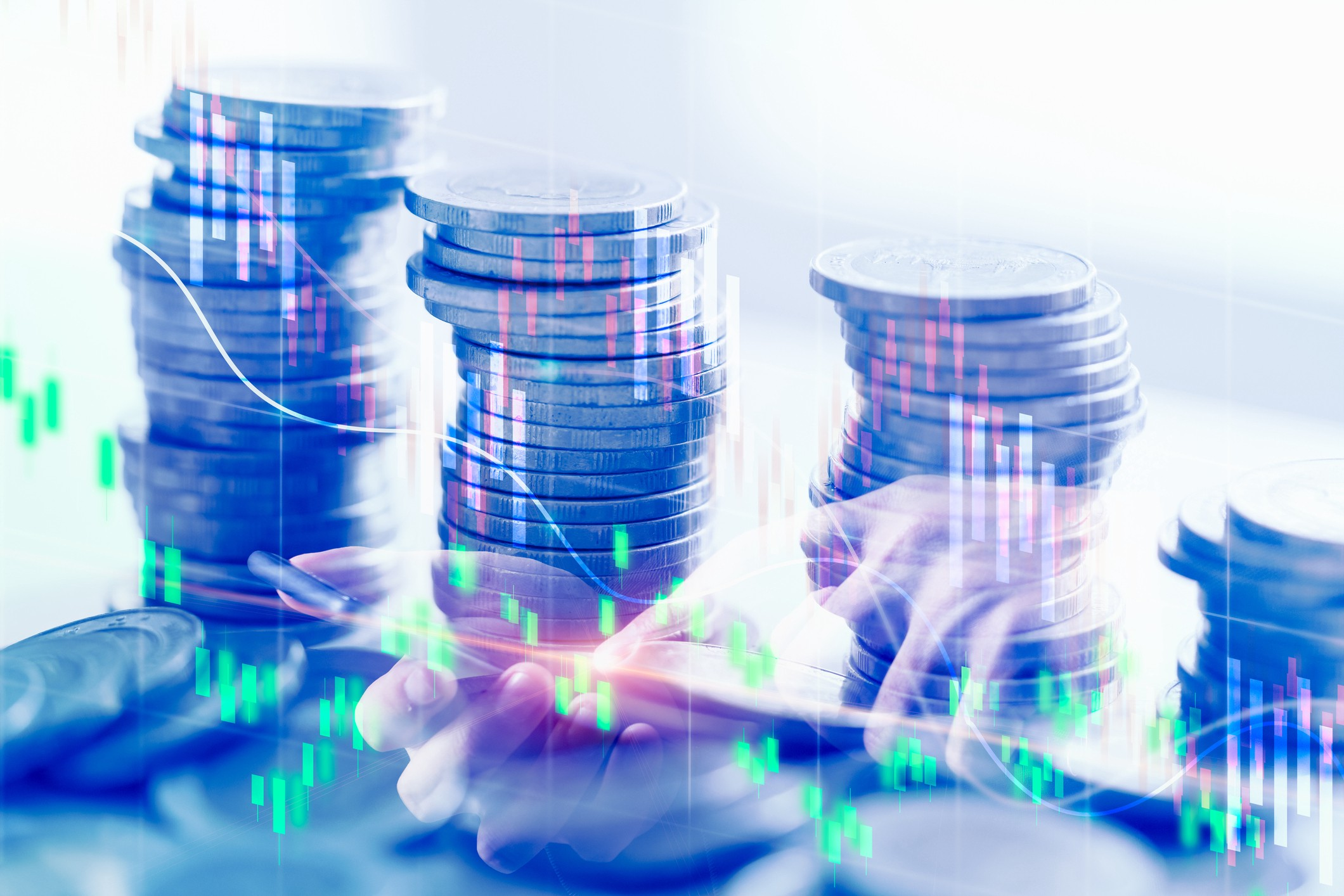 A double exposed image with a stock market concept, showing stacks of coins, hands tapping a smartphone, and a trading graph.