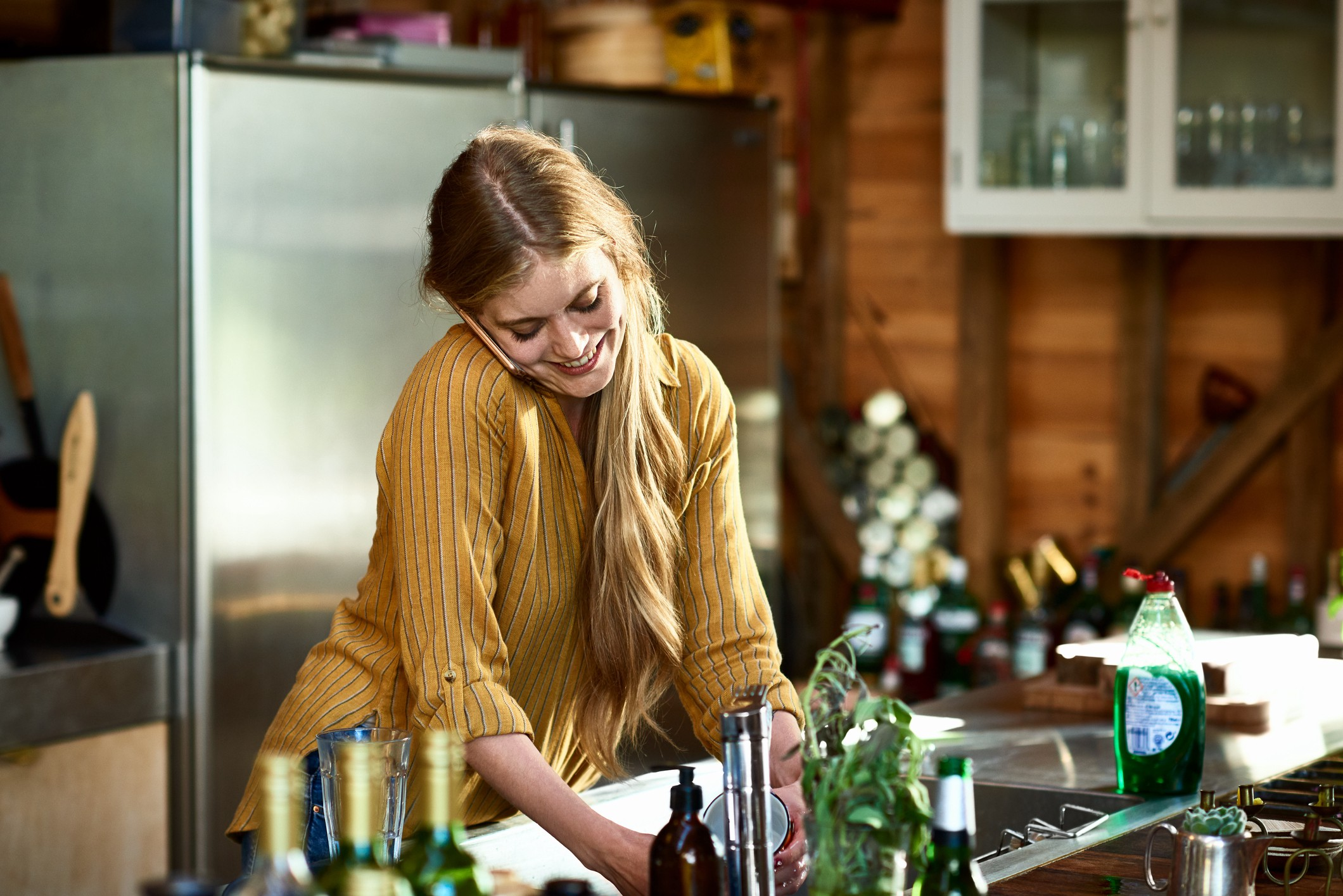 Young woman multitasking talking on the phone while washing dishes.