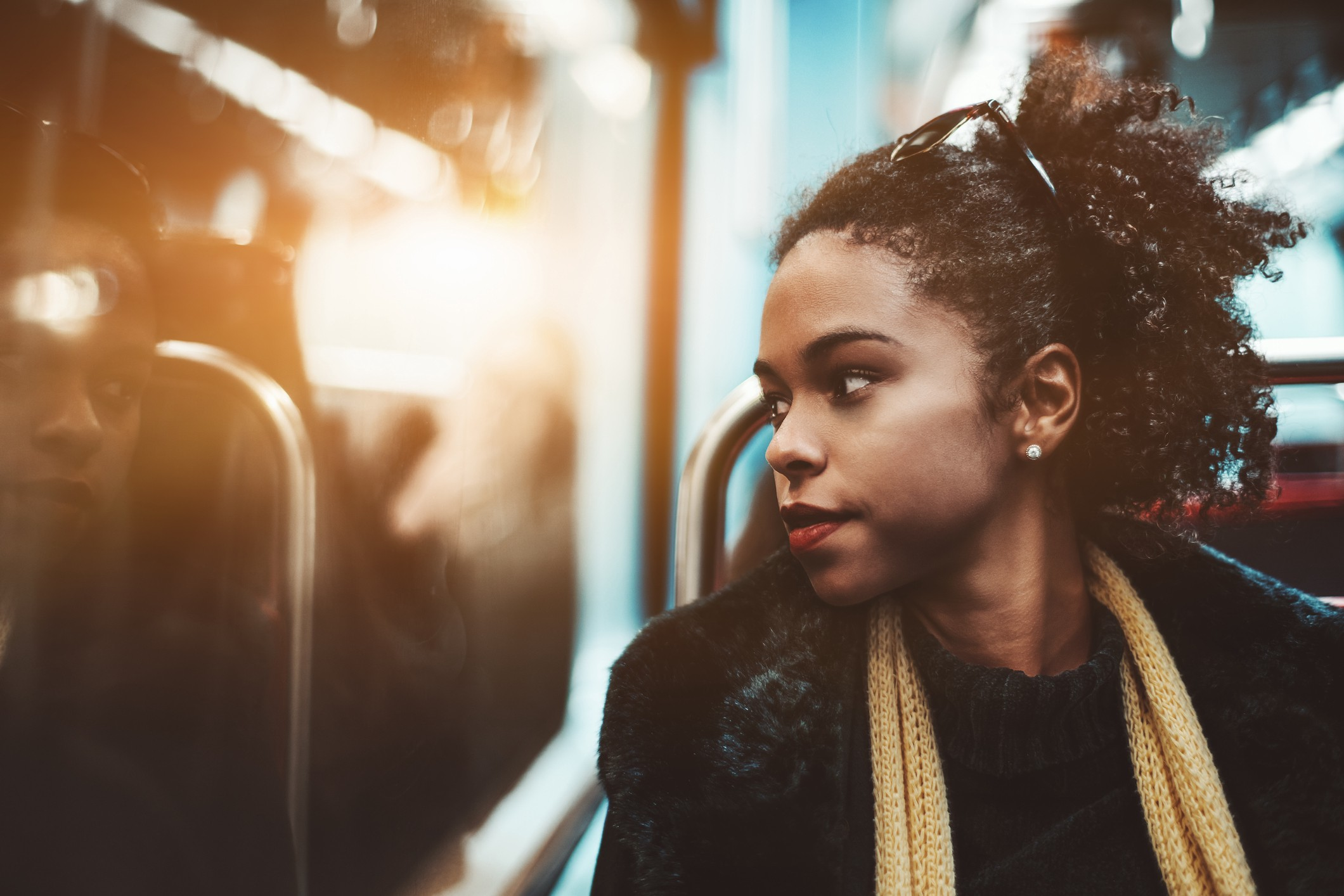 A pensive black woman looks out the window of a bus.