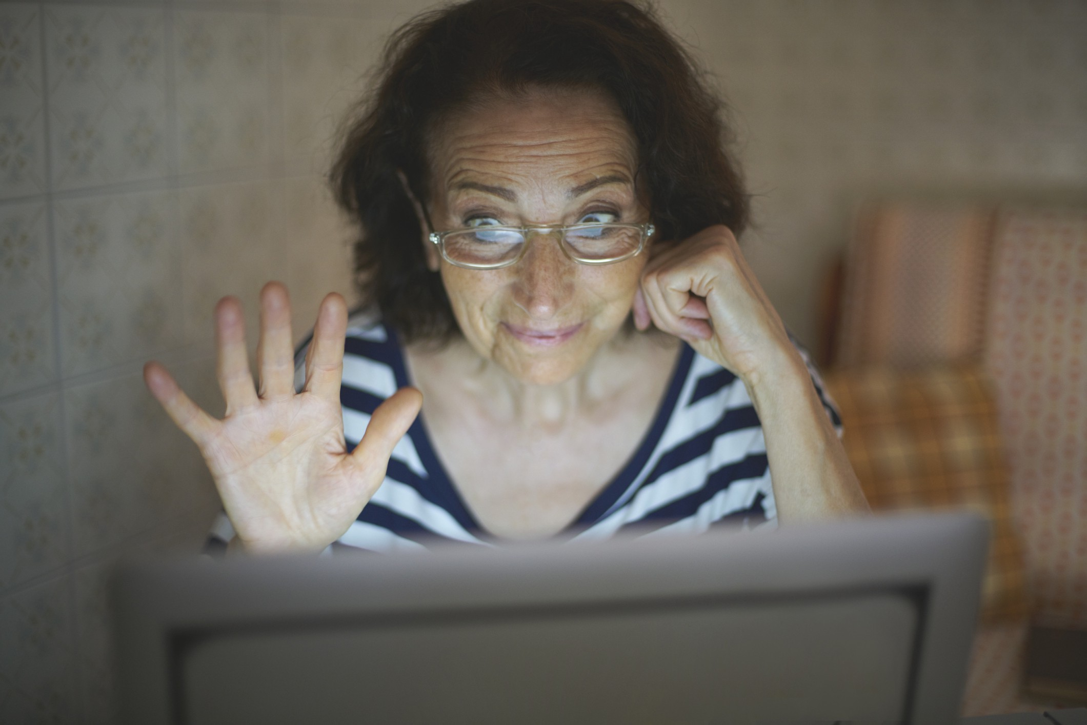 Senior woman waving hi to the Zoom call with a restrained expression.