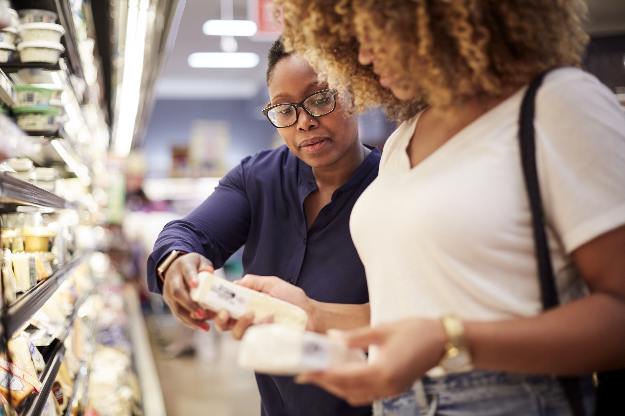 A photo of two black women examining food at the grocery store.