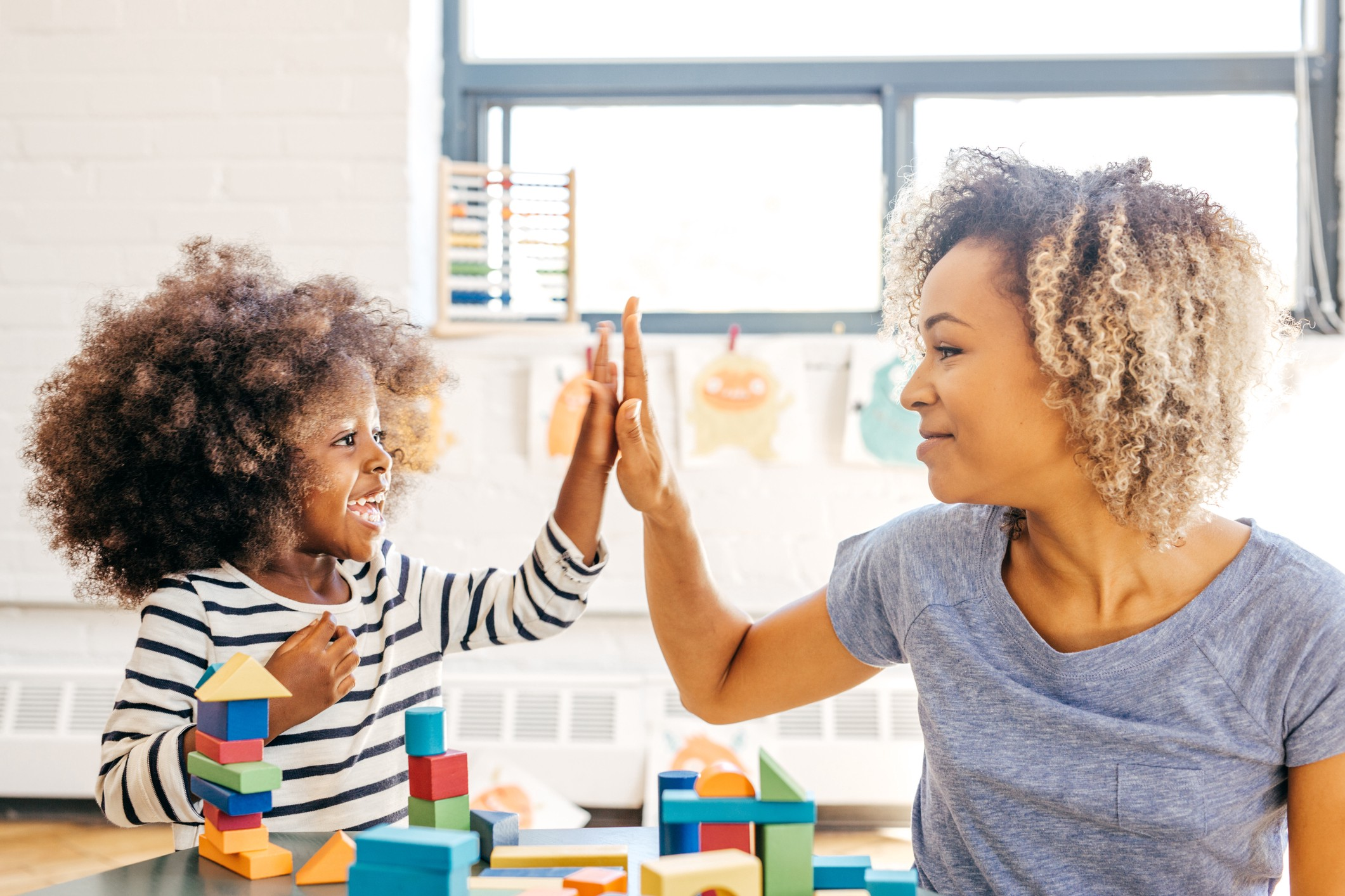 A photo of a mom and her young child high fiving as the kid plays with blocks.