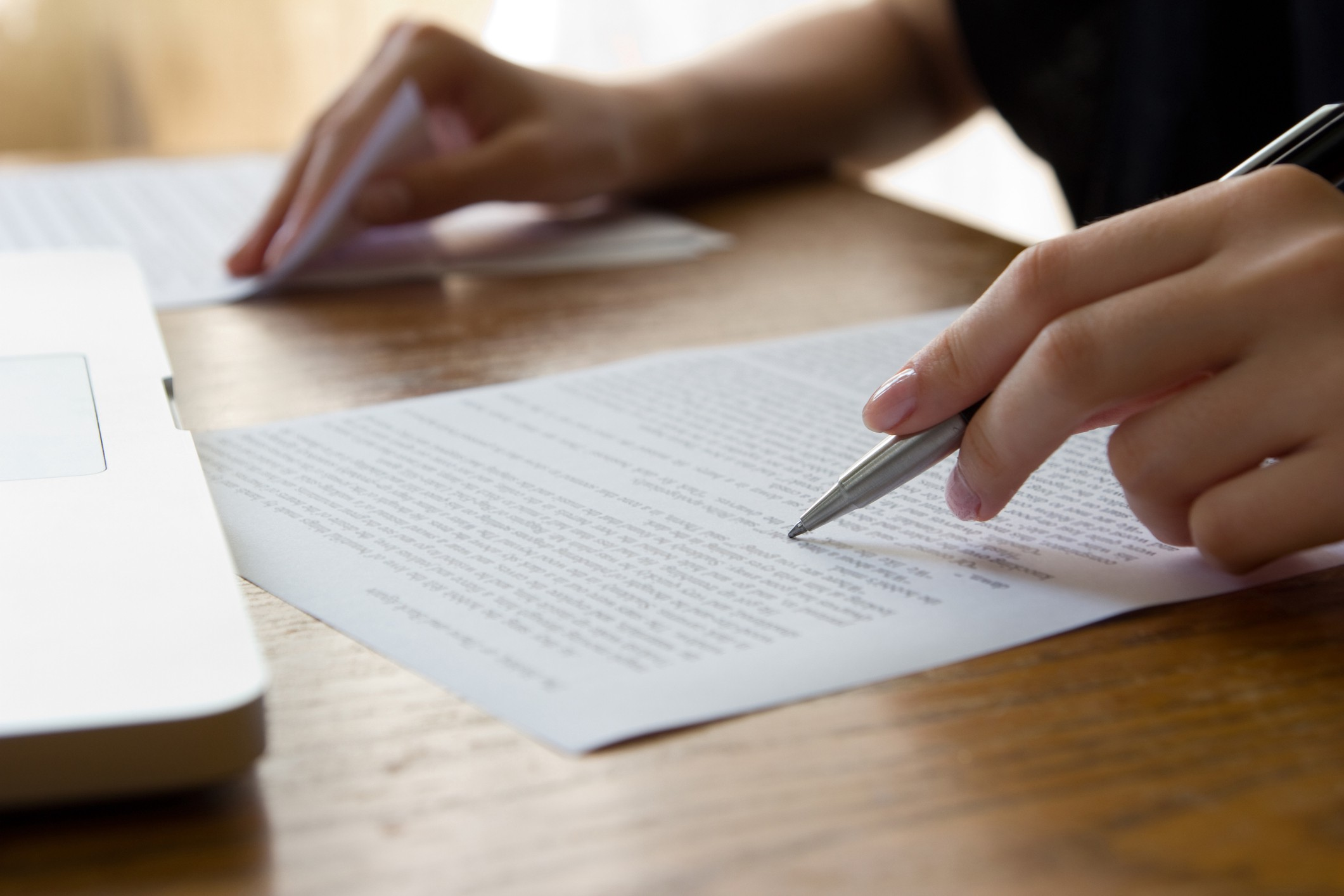 Close-up of person writing on a desk