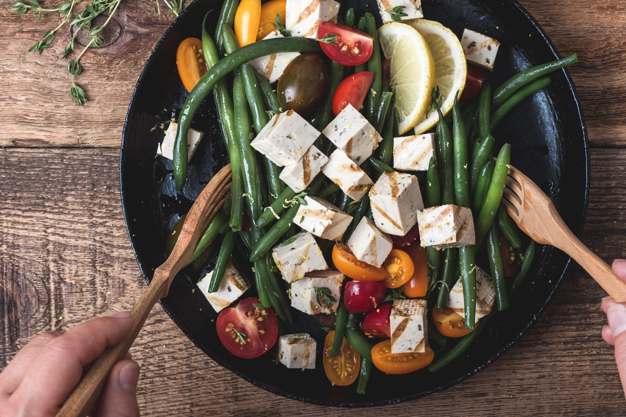 Hands using wooden utensils to toss a bowl of green beans, cherry tomatoes, and grilled tofu cubes in sauce/vinaigrette.