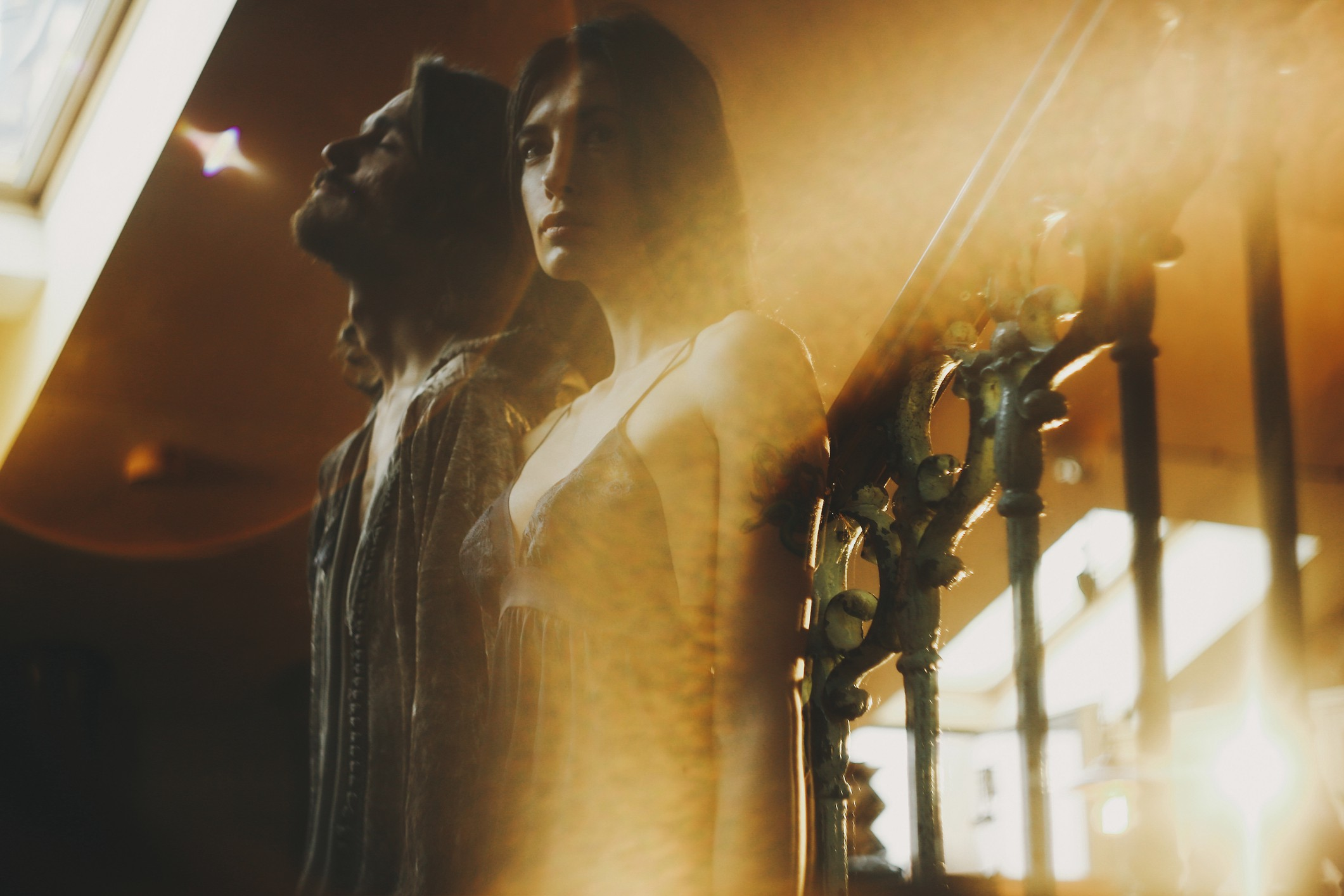 Double exposure of a couple standing on staircase against railing.