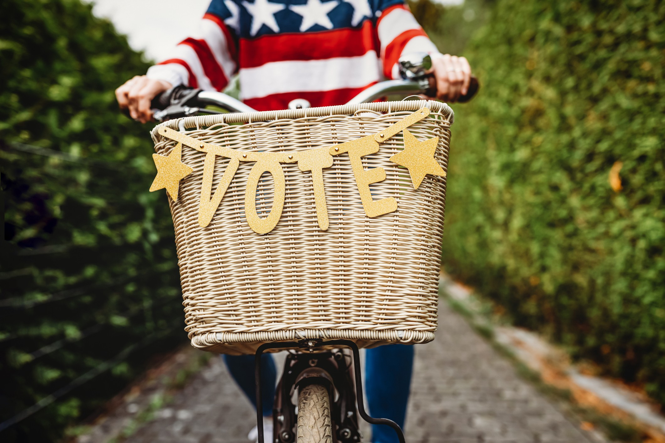 """Person riding bicycle with """"VOTE"""" banner on it."""
