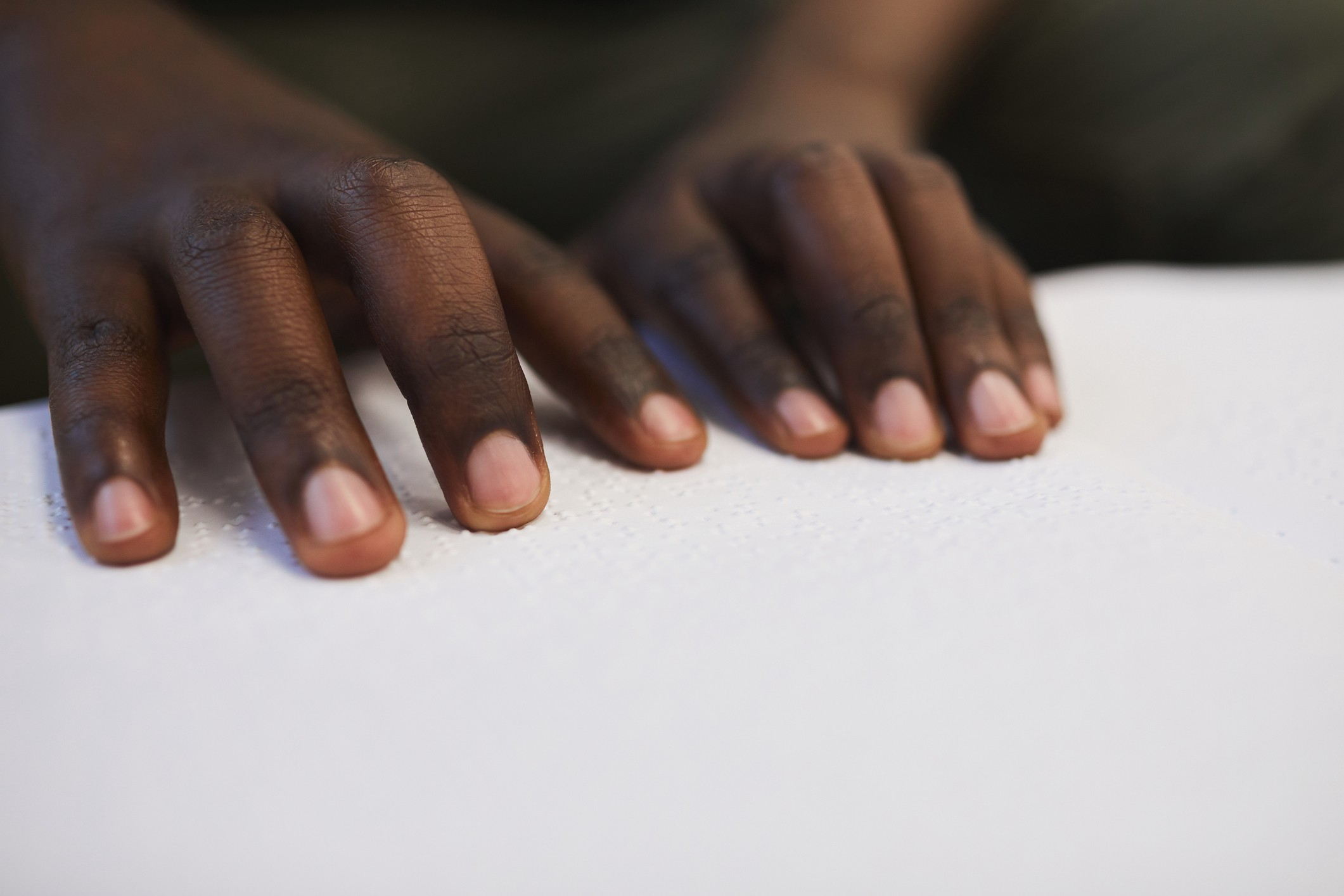 A closeup photo of a black person's hands reading Braille.