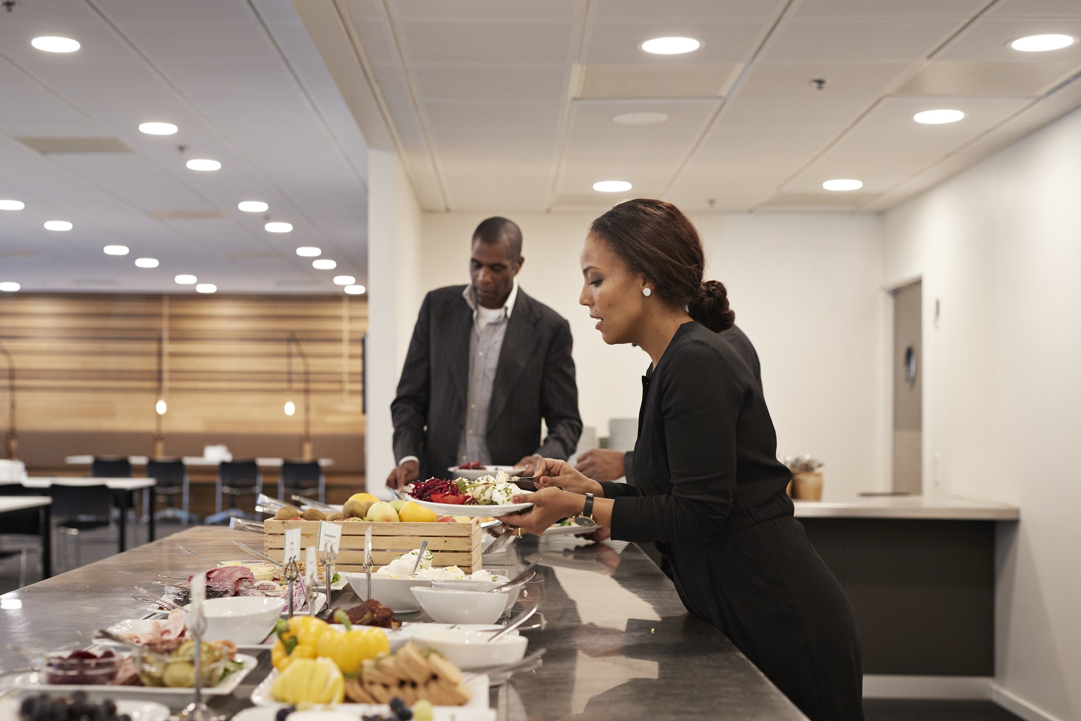 A photo of businesspeople getting food at a lunch buffett.
