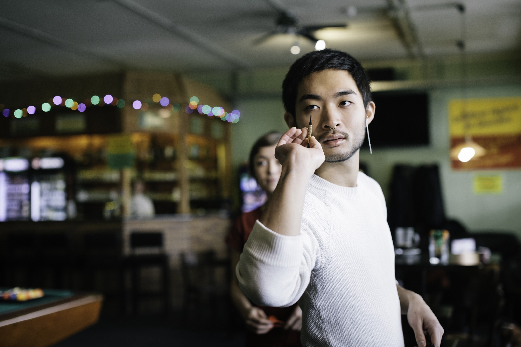 A man prepares to throw a dart with a focused expression.