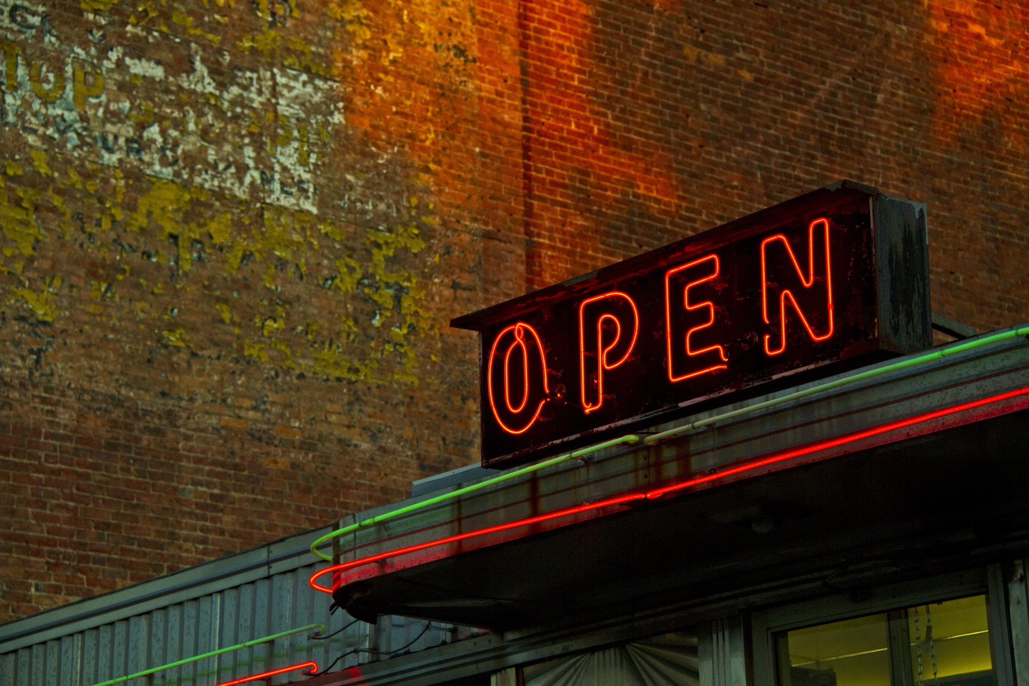 A photo of a neon OPEN sign on top of a business storefront.