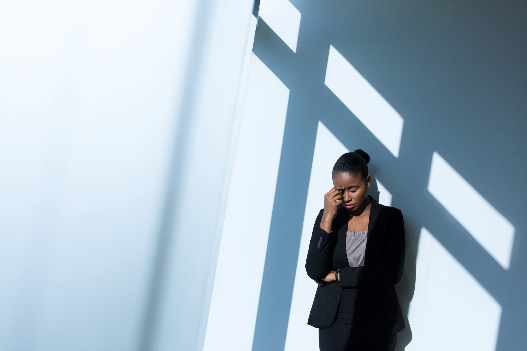 A photo of a stressed black woman at work. She is standing against a wall, wearing business casual clothes, eyes closed.