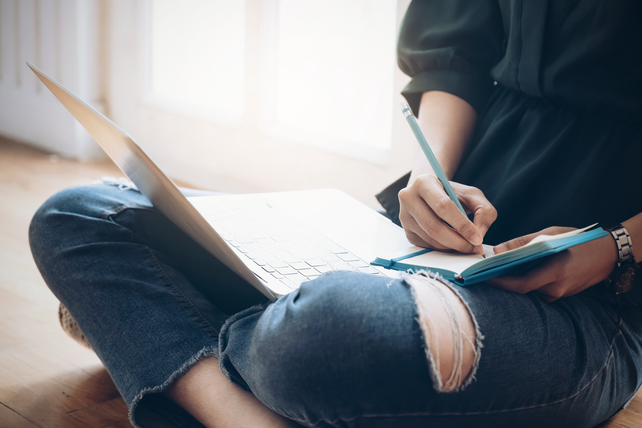 A photo of a woman writing in her journal while her laptop is on her lap.