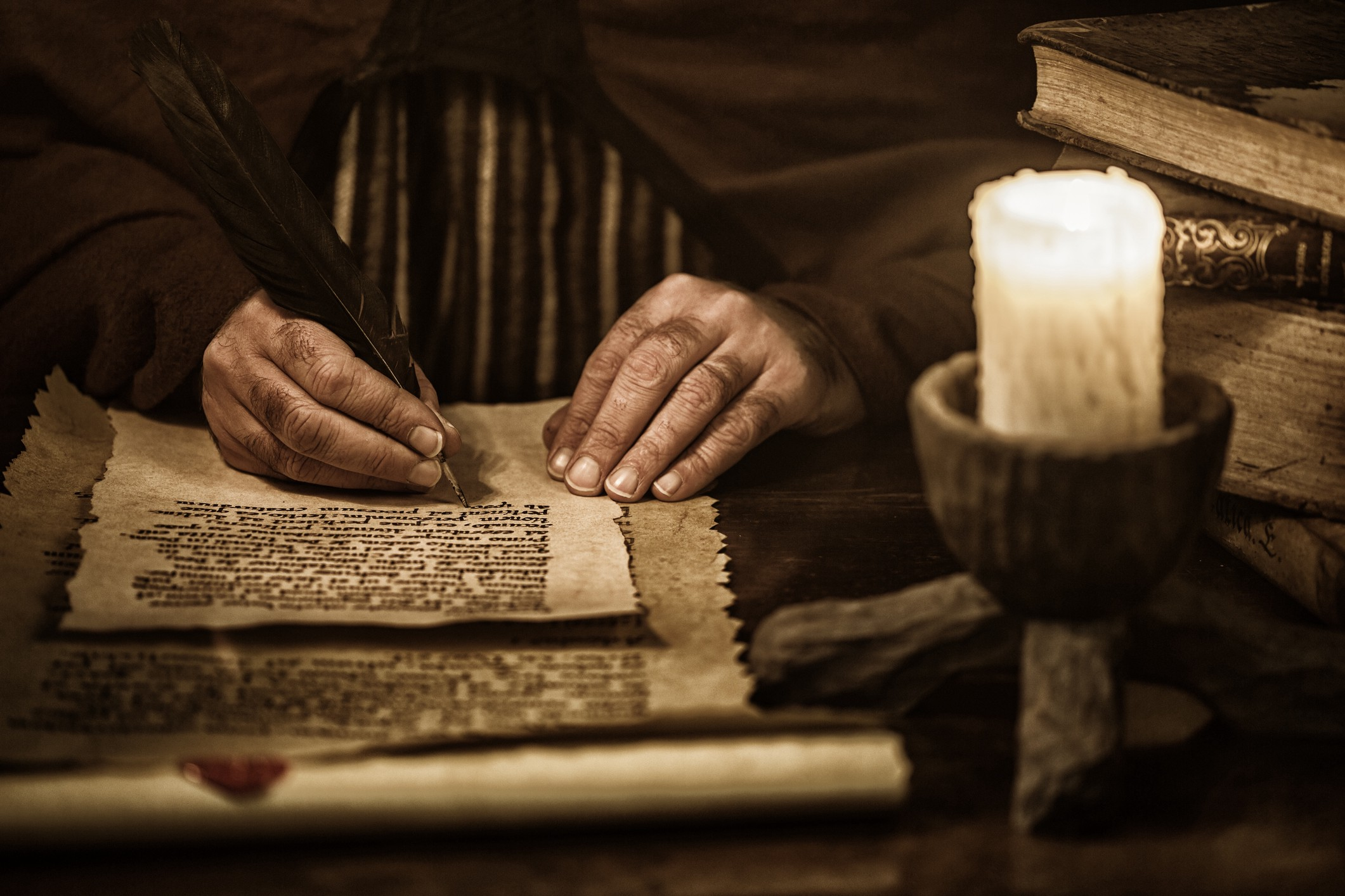 Close up of a man's hands writing on parchment in a dark room with candle and old books piled up nearby.