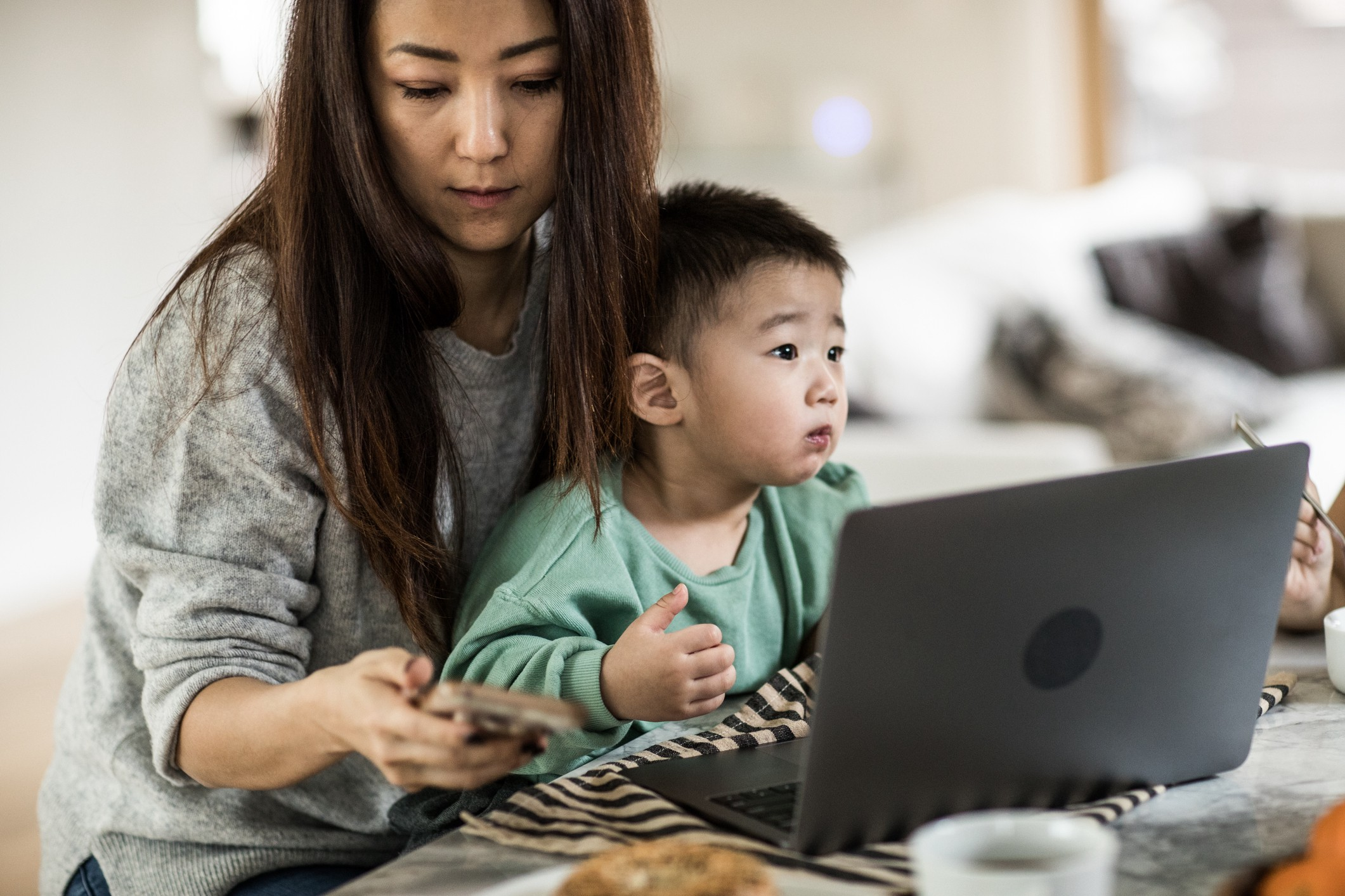 A photo of a mom working on her laptop while her son sits in her lap, she looks busy and tired.