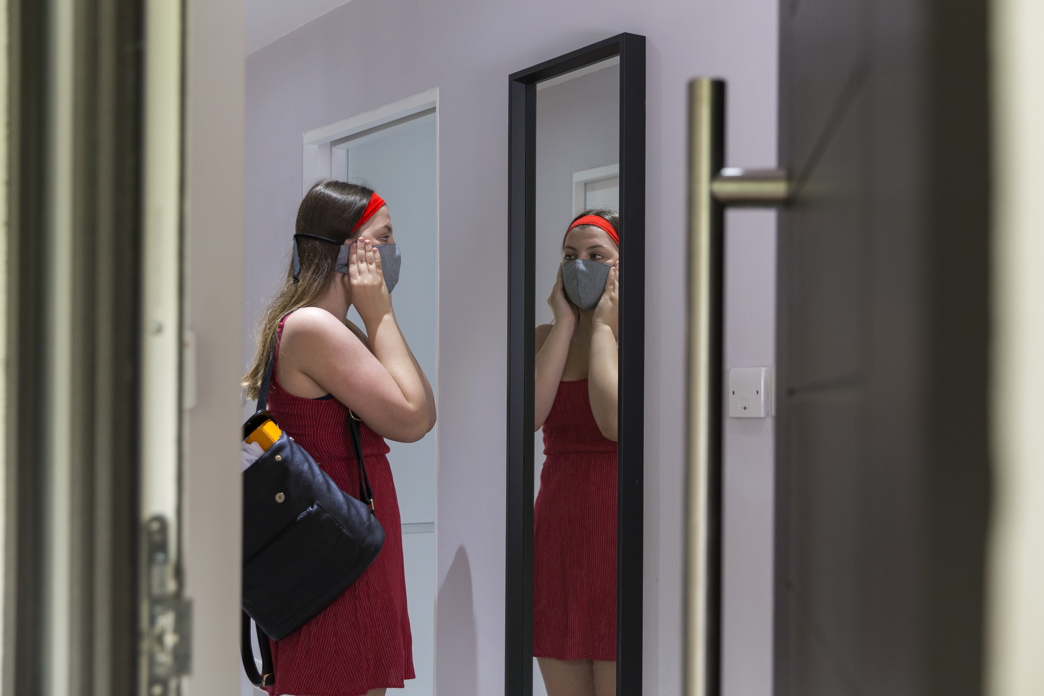 A photo of a girl putting on a face mask while preparing to go outside.