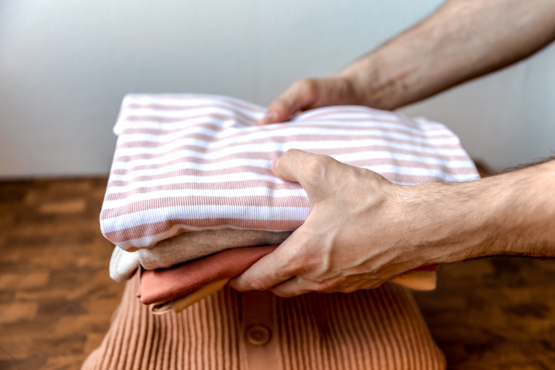 Man holding folded clothing