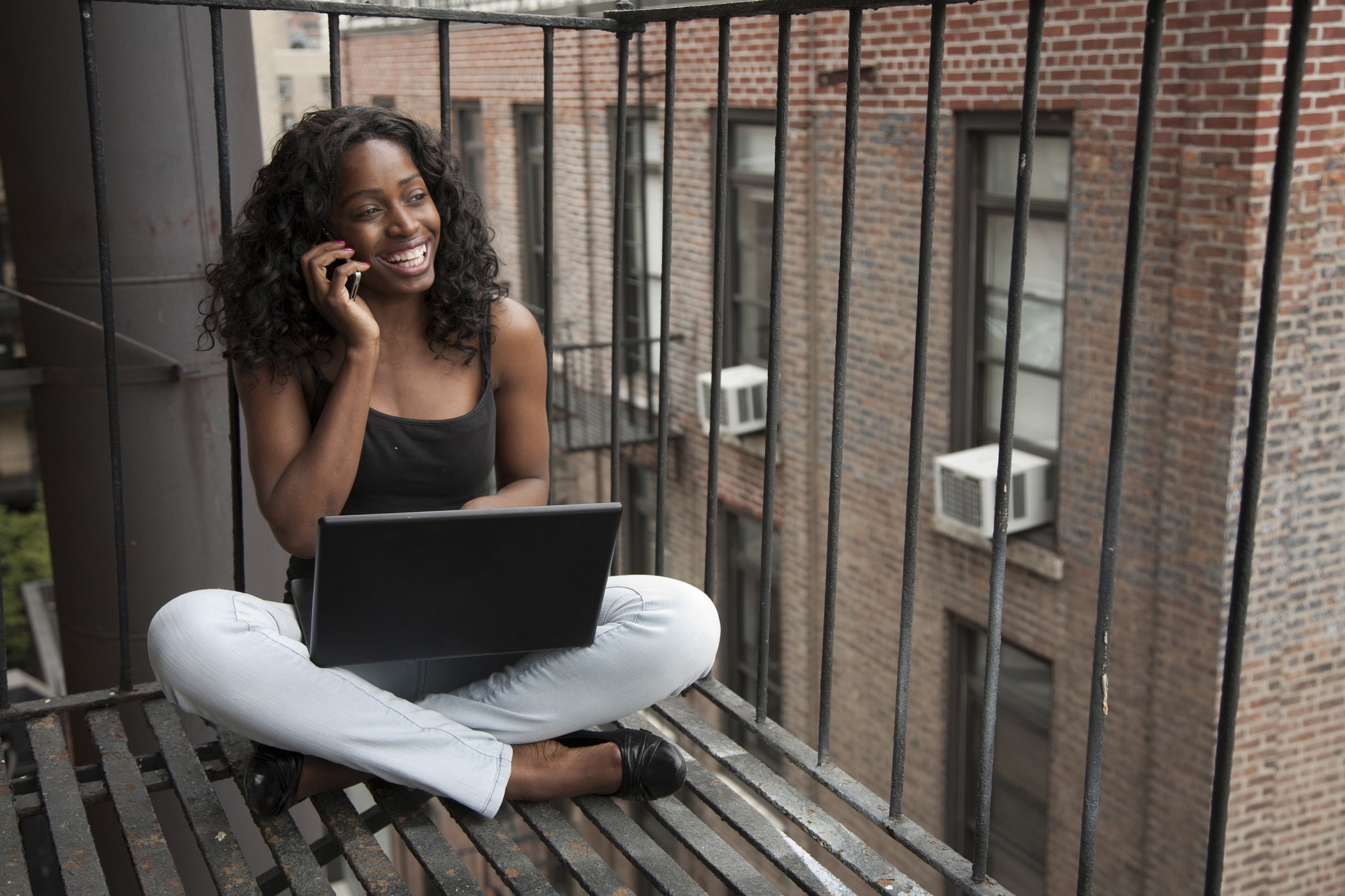Smiling Black woman sitting on a terrace with her laptop, on a phone call.