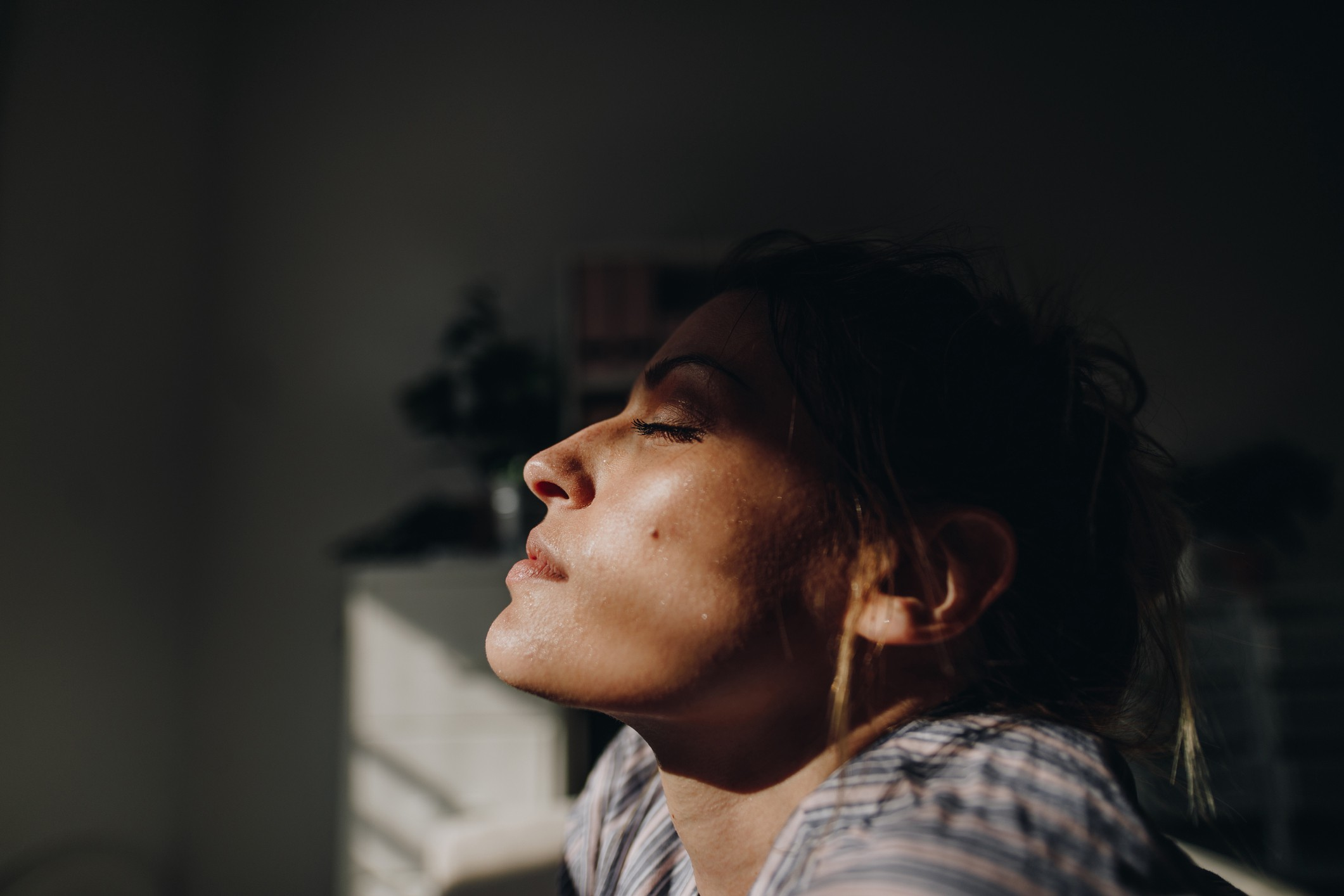 A young woman closes her eyes and breathes in, coping with loneliness and isolation.
