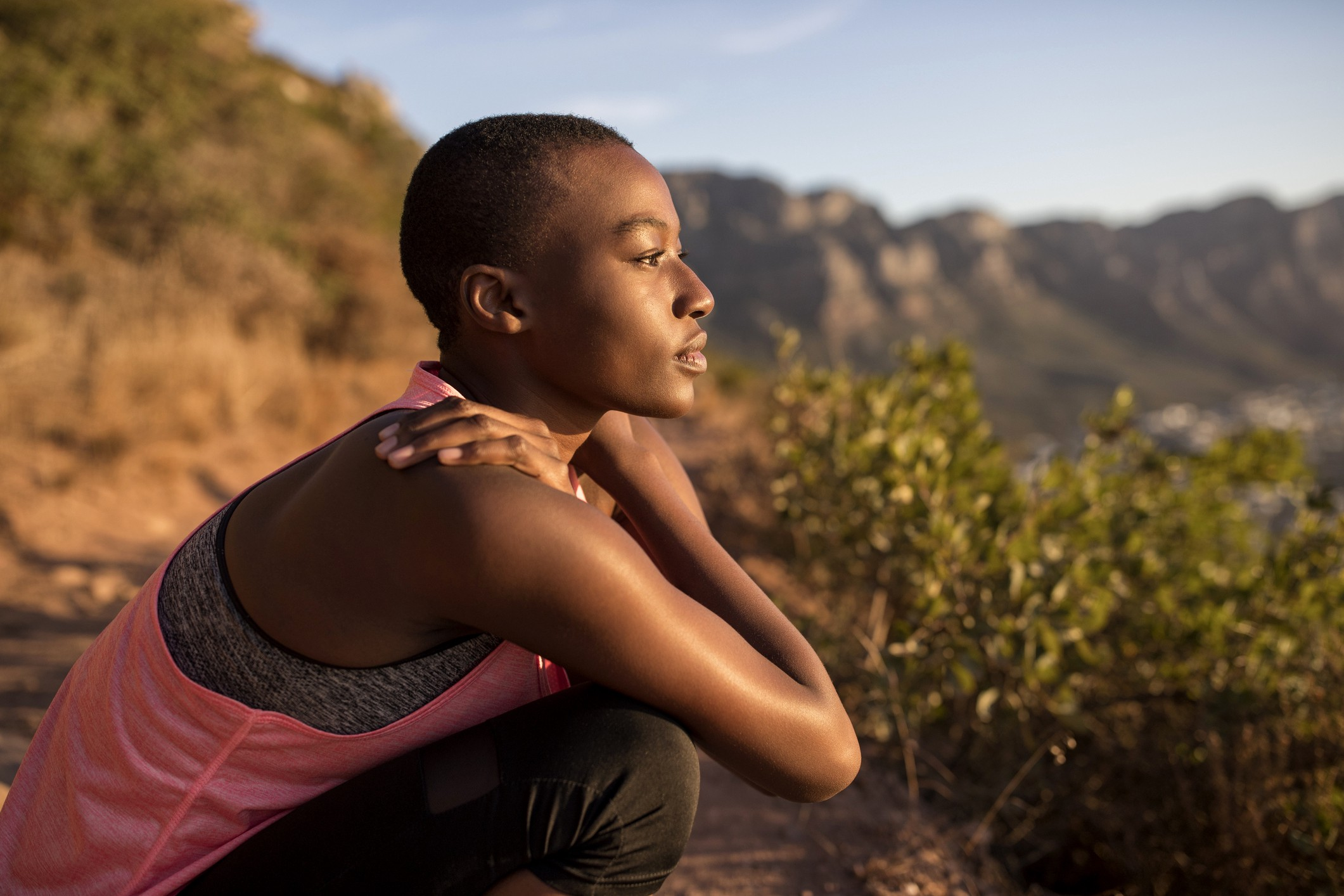 A photo of a peaceful black woman looking out at the view while taking a break on a hike.