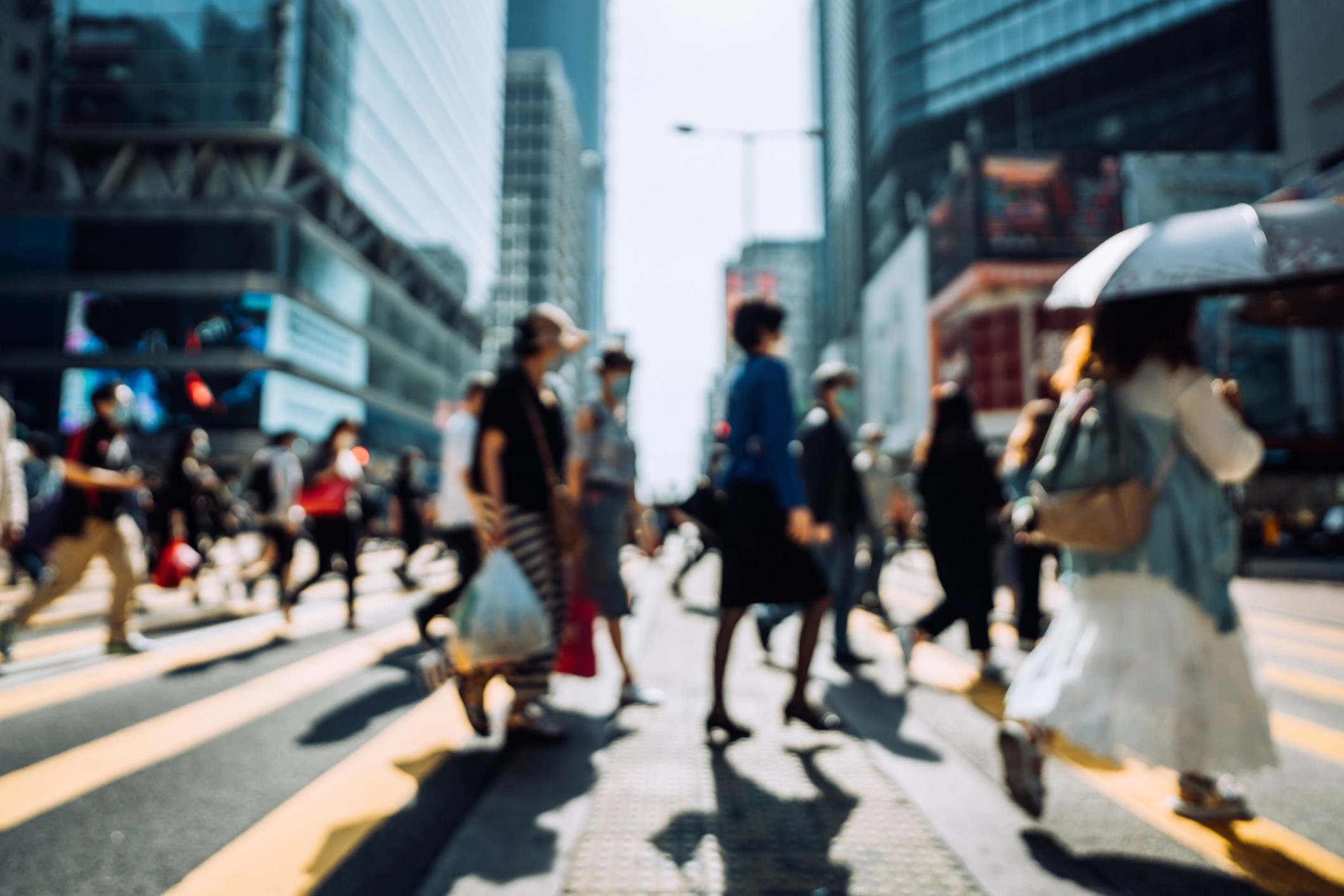 Blurred image of people walking at a crosswalk in a city.