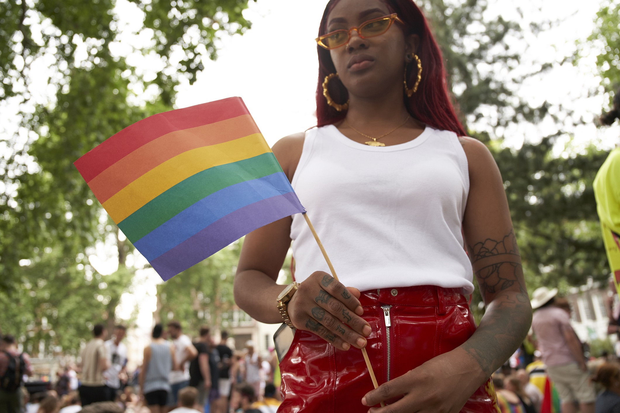 A young black woman holds up a rainbow flag at an outdoor gathering.