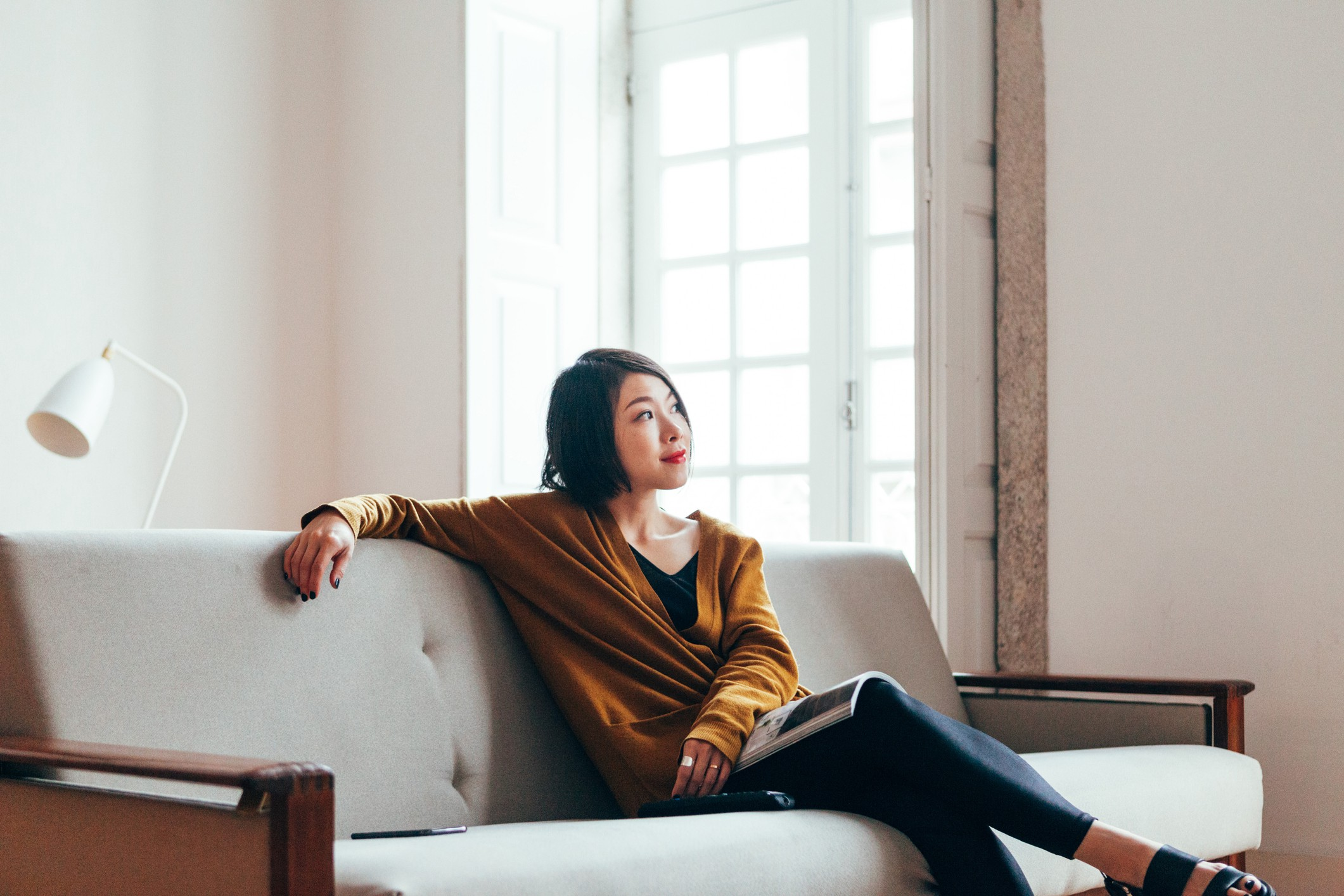 Asian woman sitting on her sofa looking out the frame.