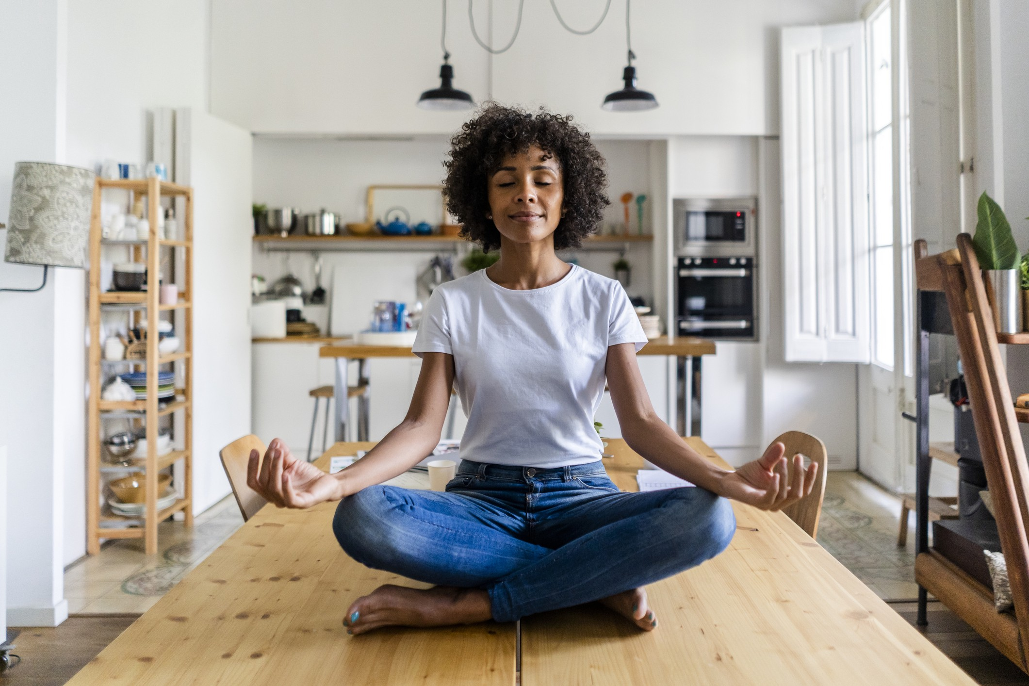 A photo of a black woman meditating while sitting on top of her table.