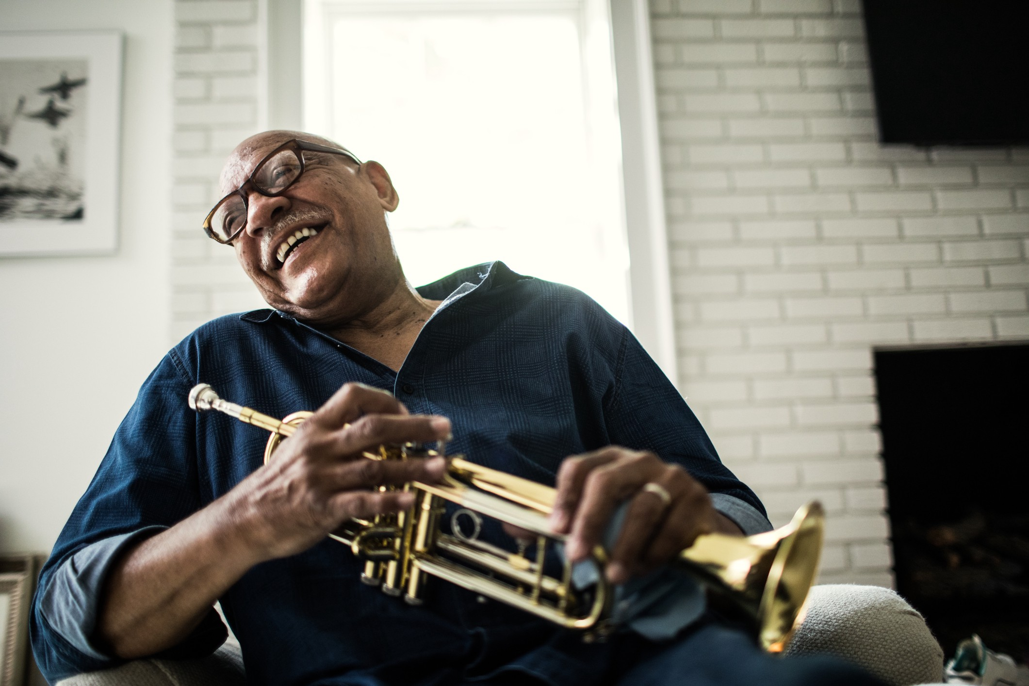 A photo of an older black man holding a trumpet in his living room. He is laughing.
