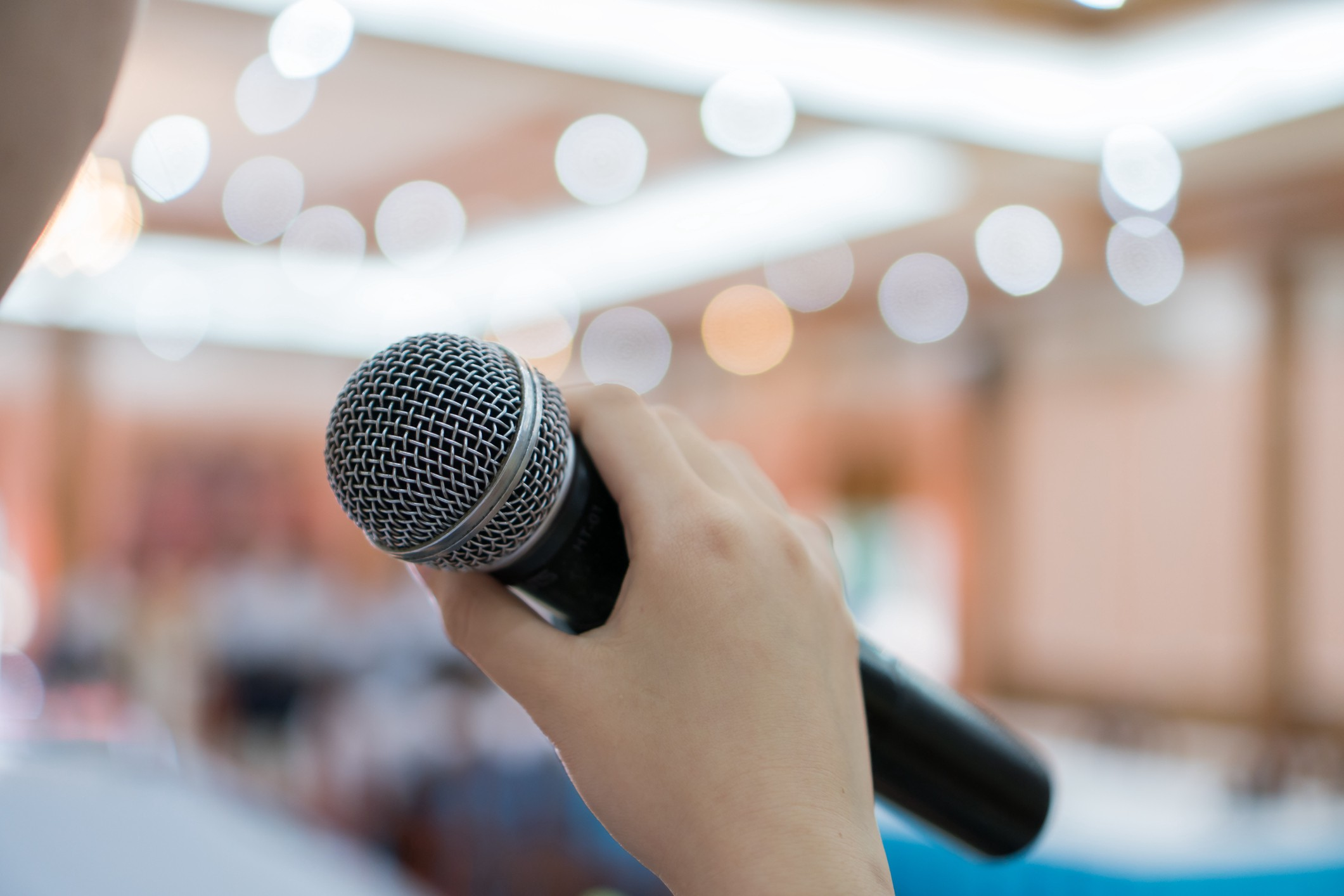 A person holds up a microphone.