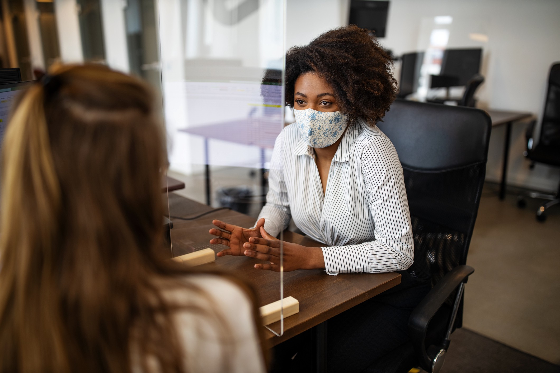 A Black businesswoman wearing a face mask negotiates with a client. There is a plastic divider for social distancing.
