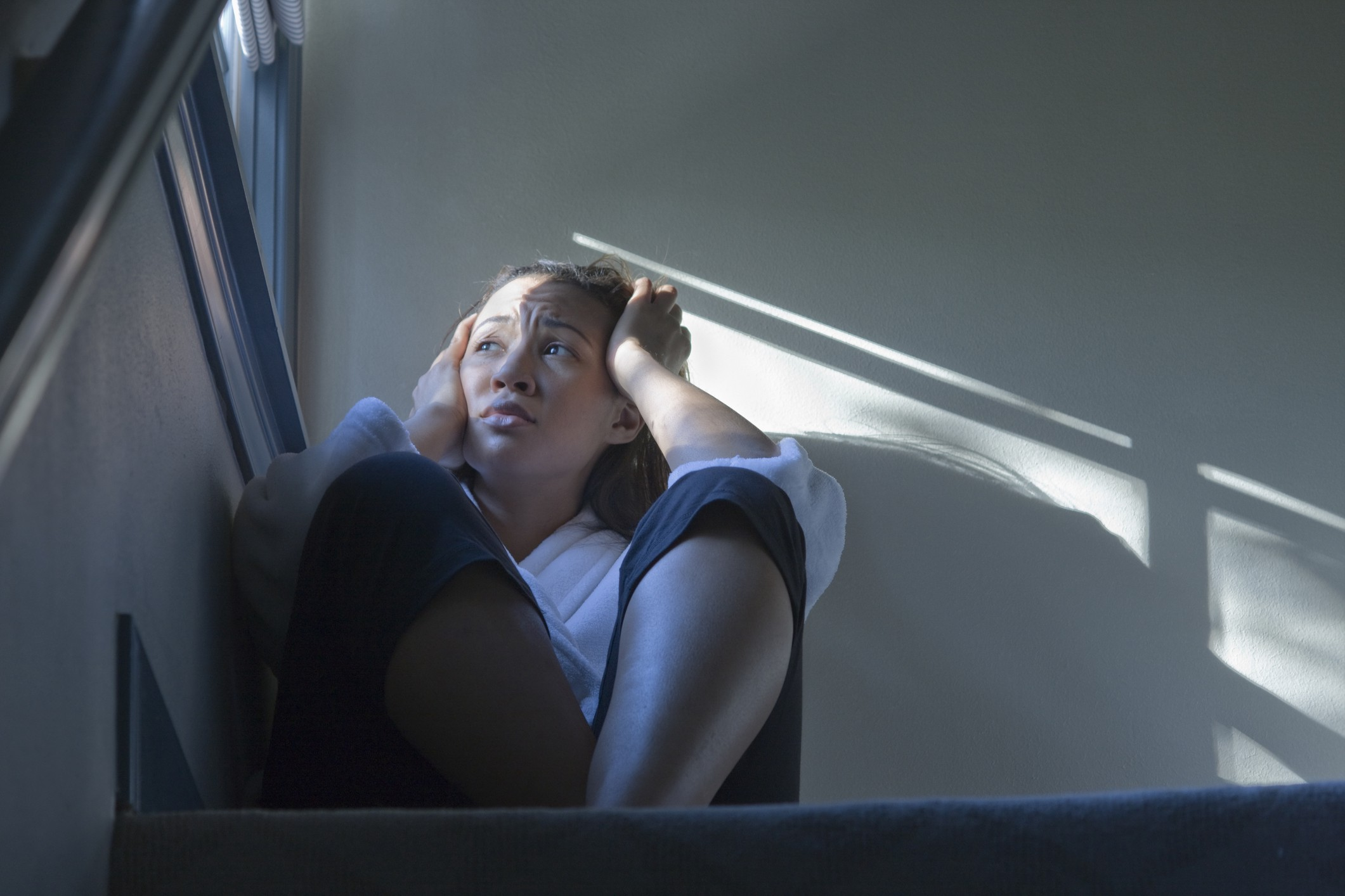 A photo of a despondent black woman sitting by the window in the stairwell.